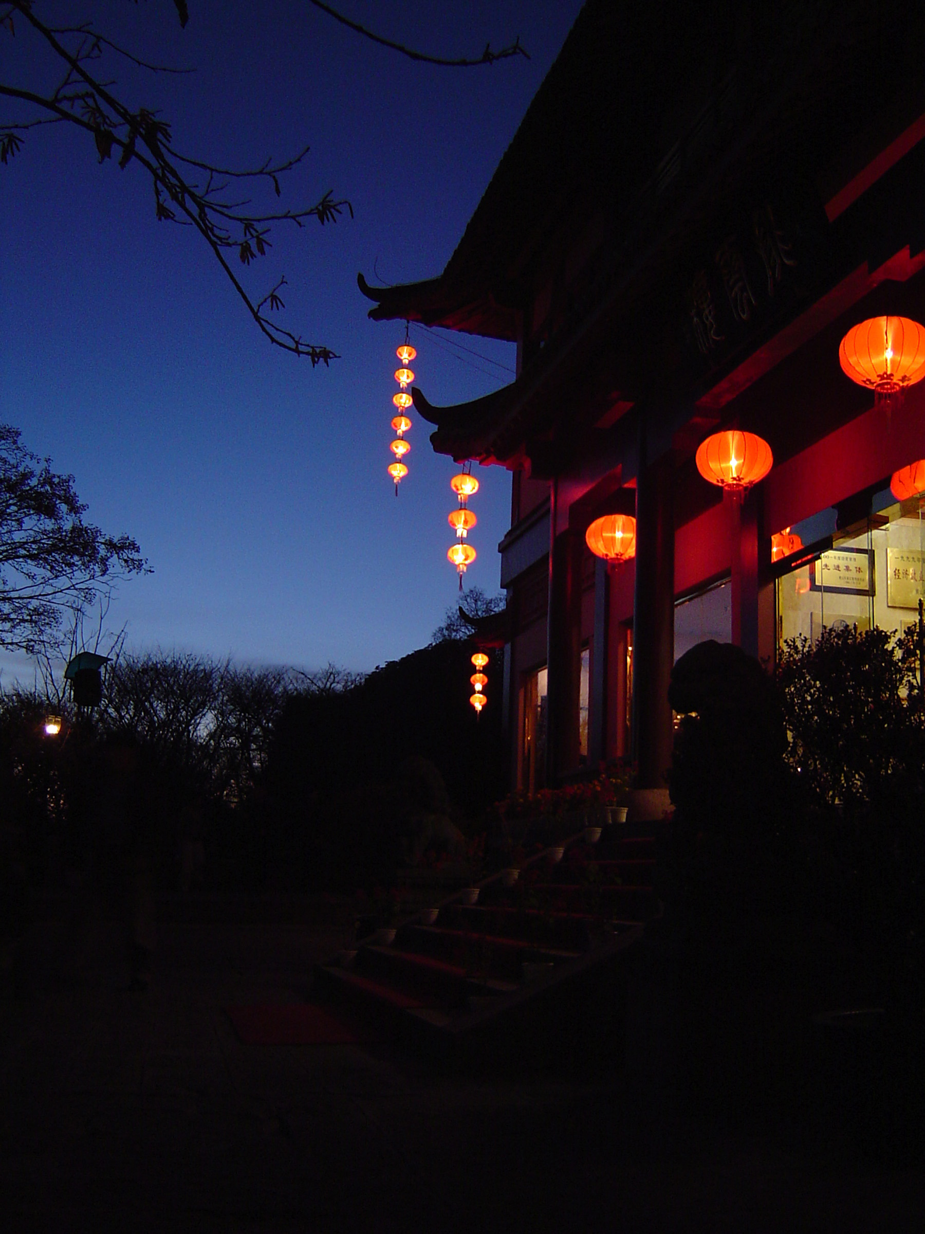 Night scene of a traditional Chinese house with colorful lighted lanterns hung at the entrance as a welcome to visitors