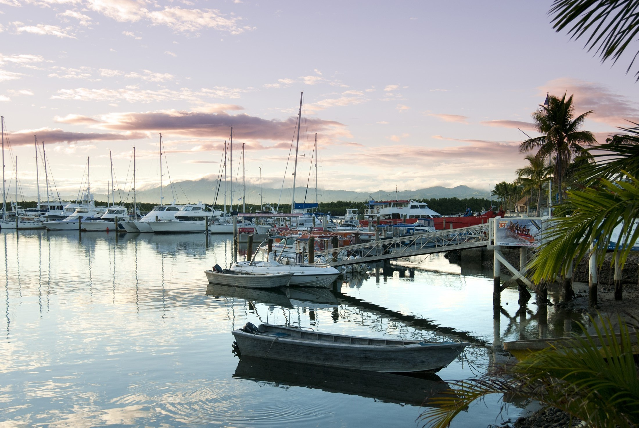 Beautiful delicate pink sunset over Denarau Marina, Fiji, with pleasure boats and yachts moored in the sheltered water