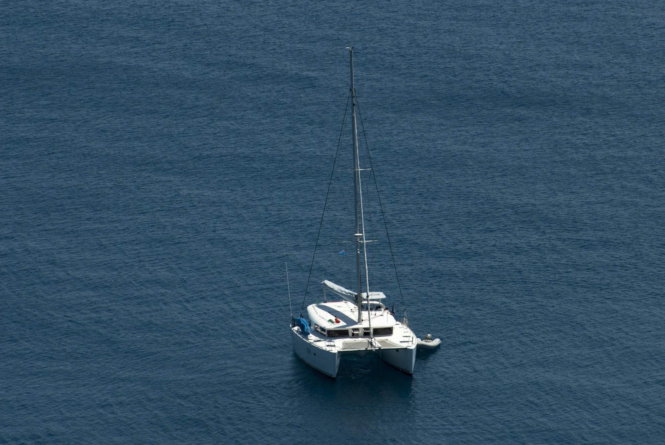 Luxury catamaran moored offshore in mid ocean with copyspace, high angle view