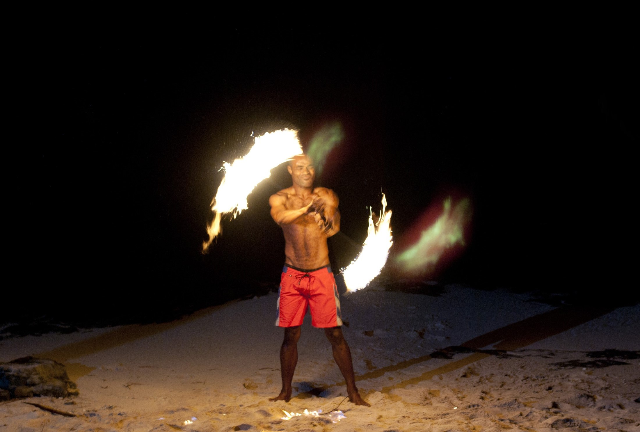 Fijian fire dancer performing with flaming branches on a sandy beach twirling them around his naked torso
