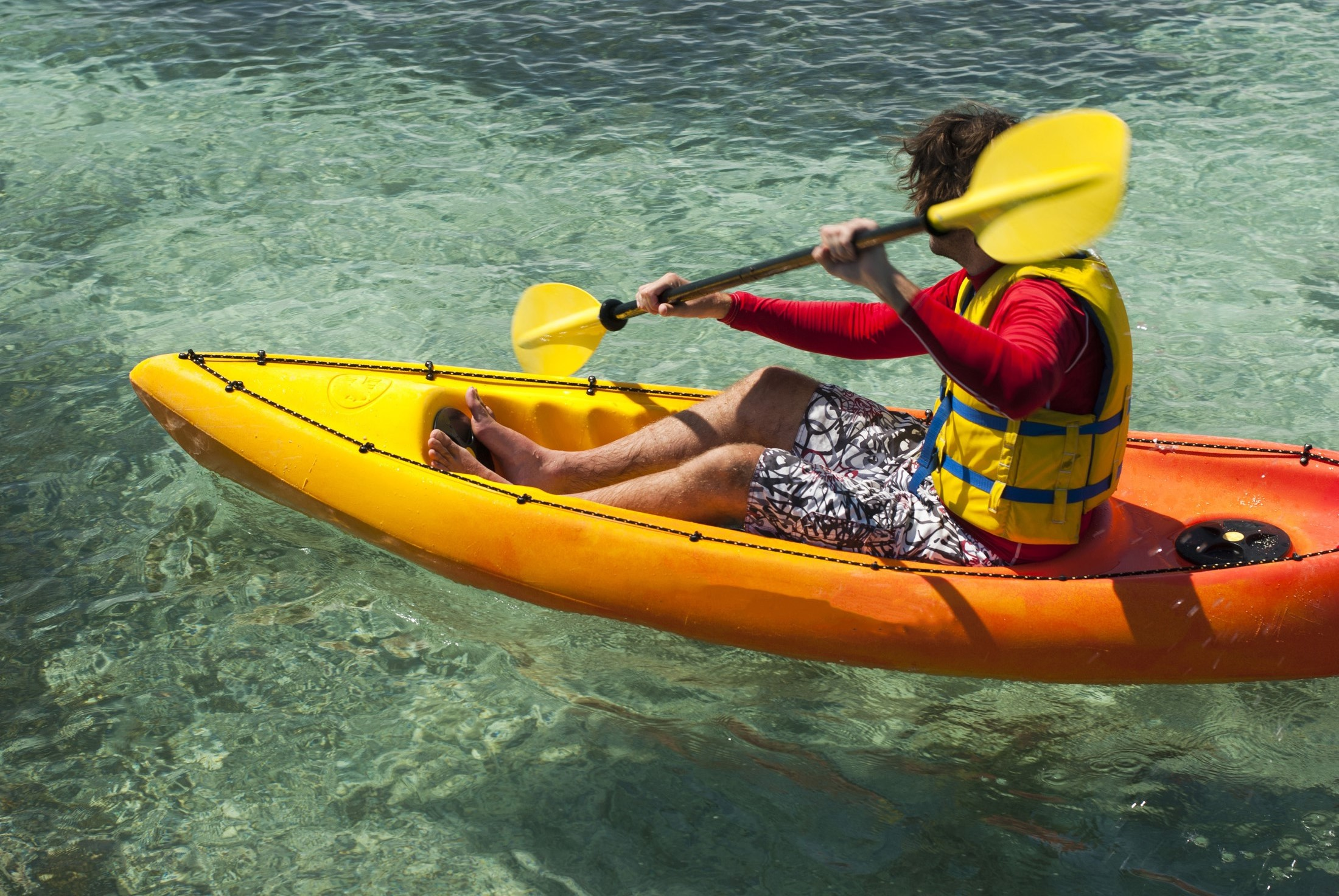 Kayaker in a small single kayak or canoe paddling in clear tropical water enjoying his summer vacation
