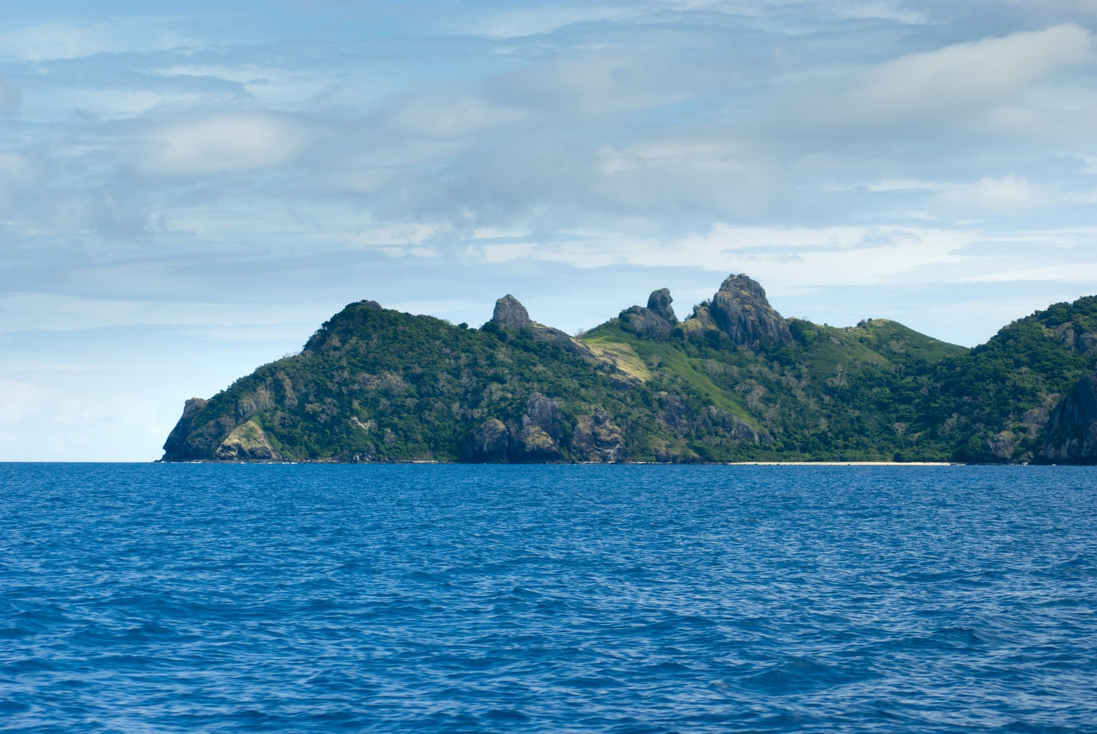 View across open blue ocean while cruising offshore of Yasawa Islands Fiji showing the rocky topography of these beautiful tropical islands