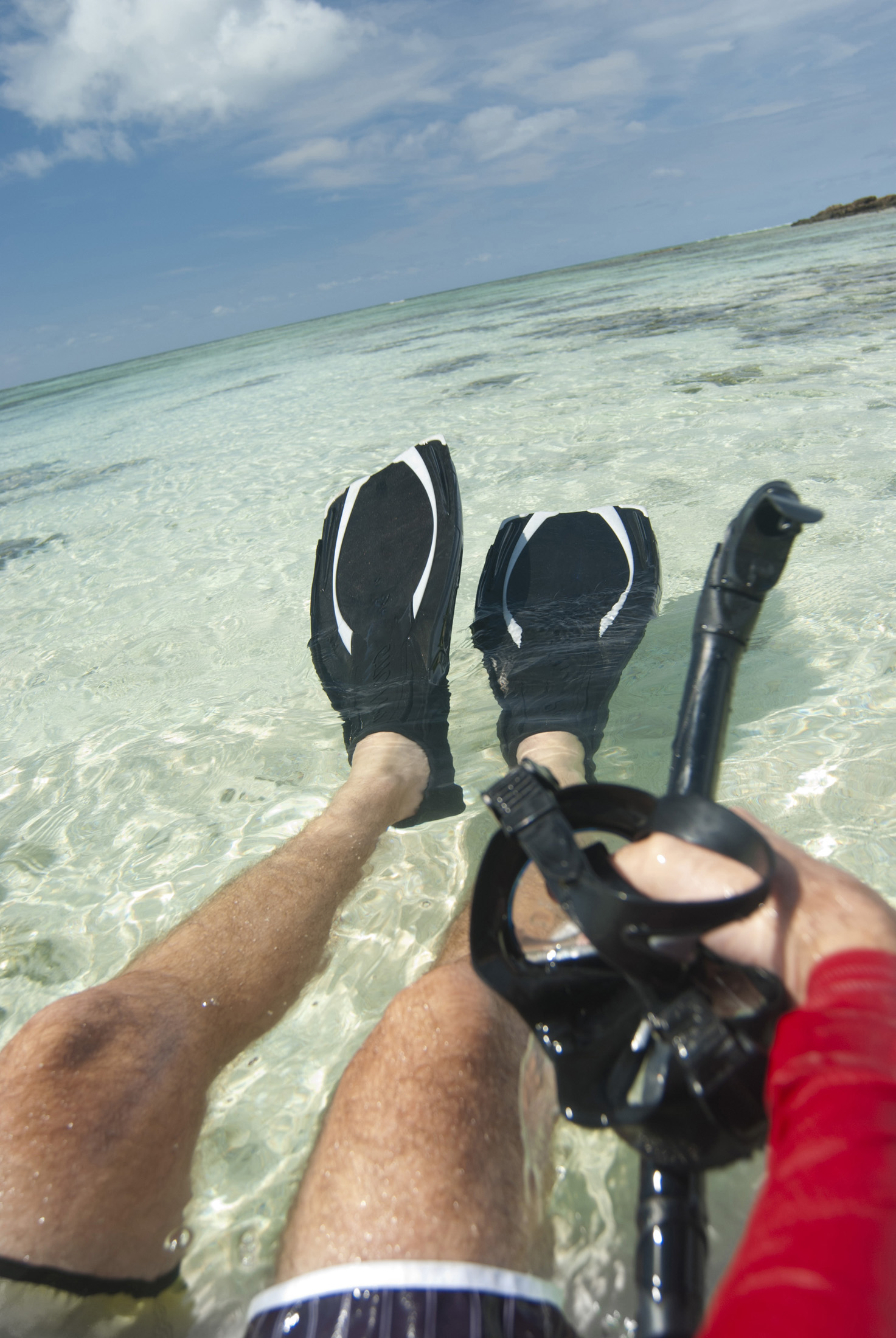 Cropped view of a man floating in crystal clear tropical water wearing flippers with a snork and goggles in his hand