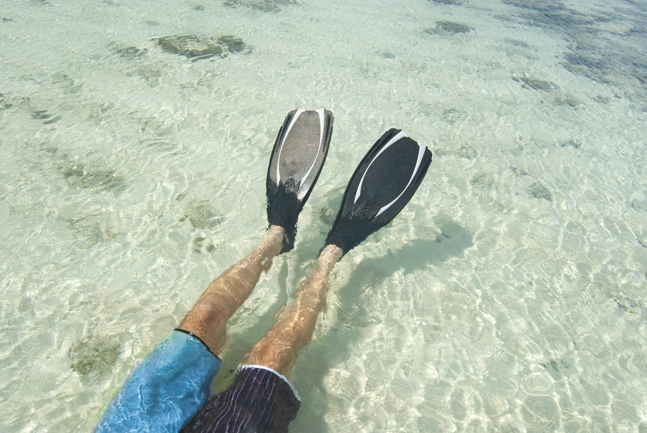 Man lying on his back wearing a pair of fins snorkeling in clear tropical water off a Fijian island