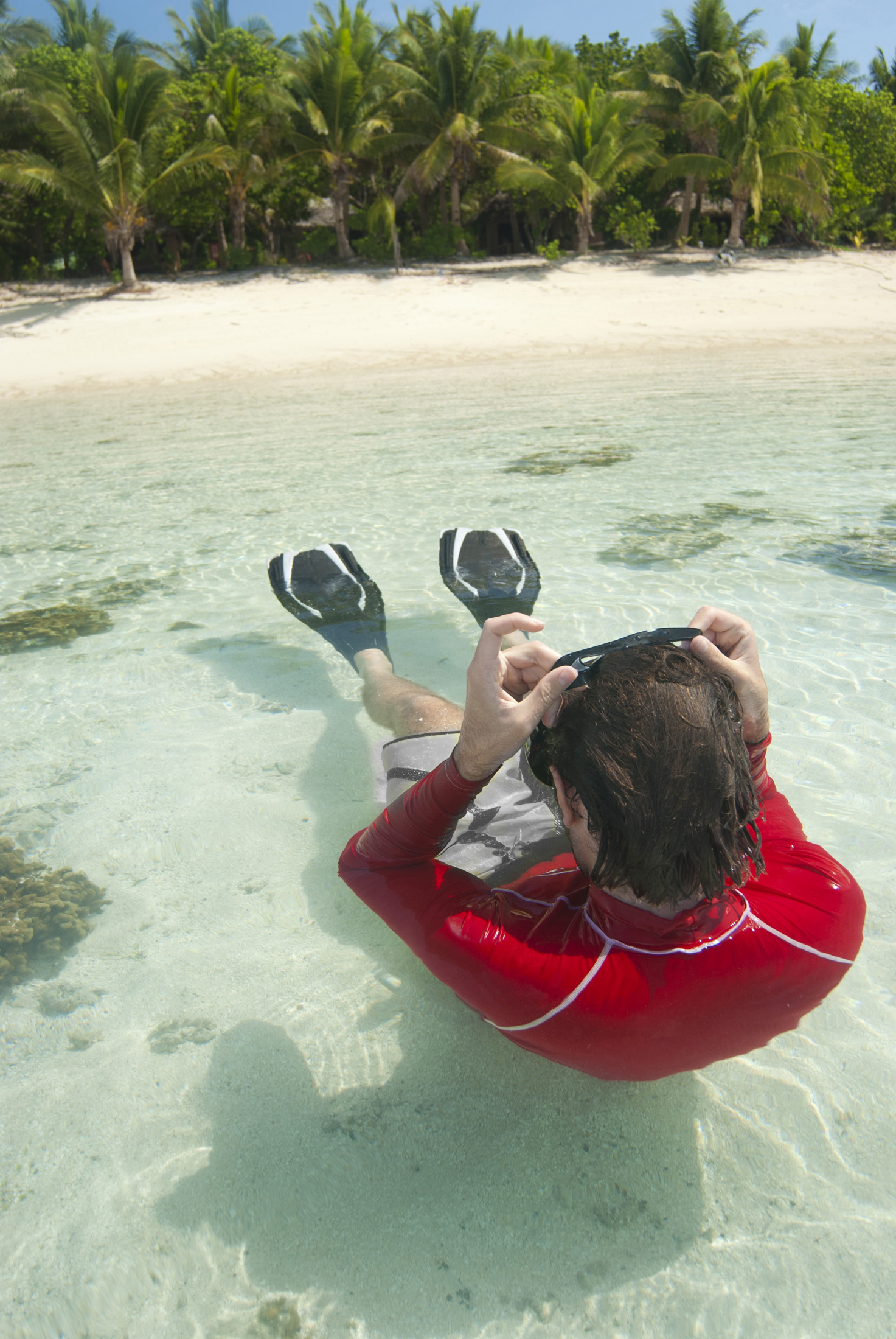 Man snorkeling in shallow crystal clear water off a tropical island beach floating on his back clearing his goggles