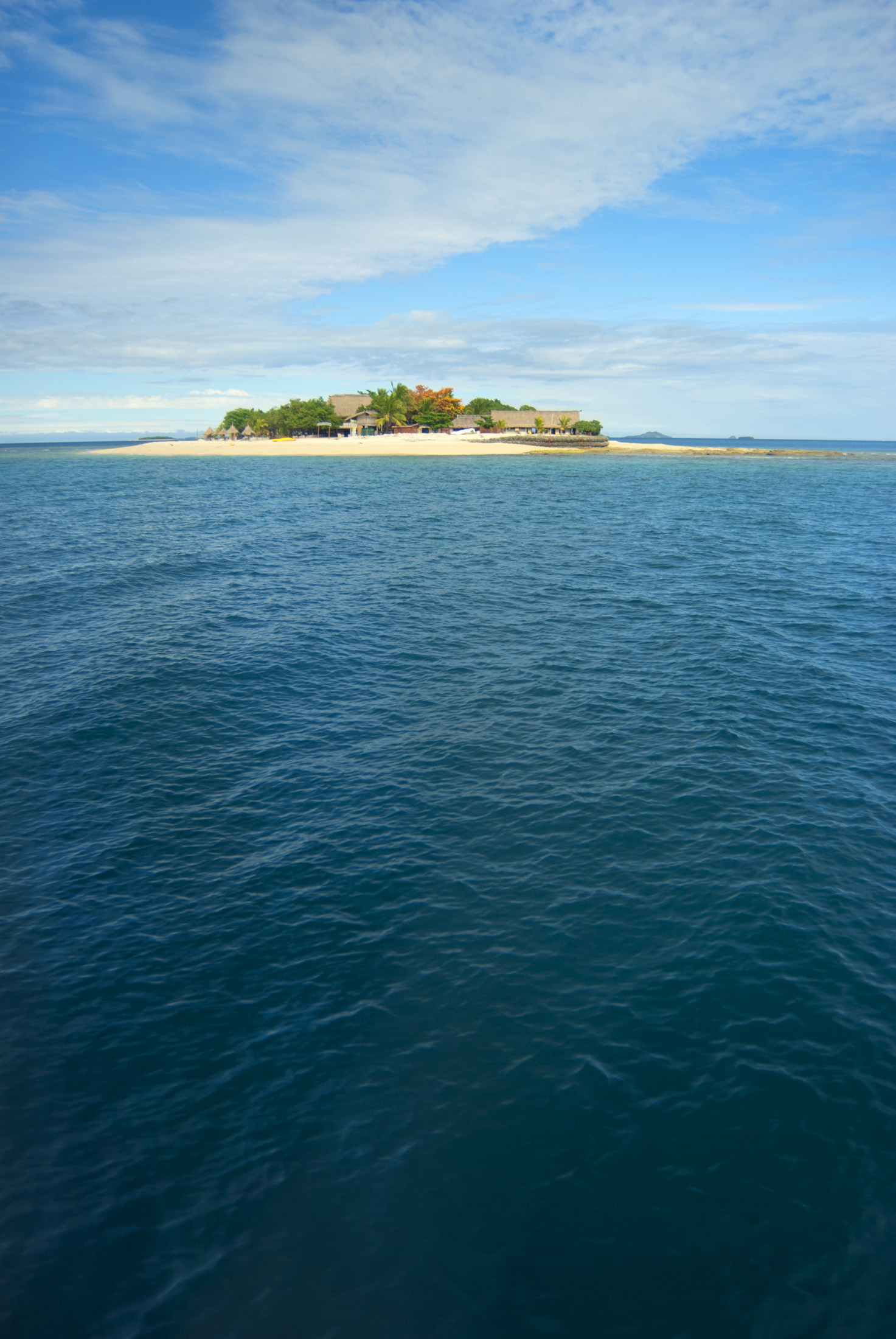 View across open ocean with copyspace to South Sea Island, an idyllic small Fijian resort island