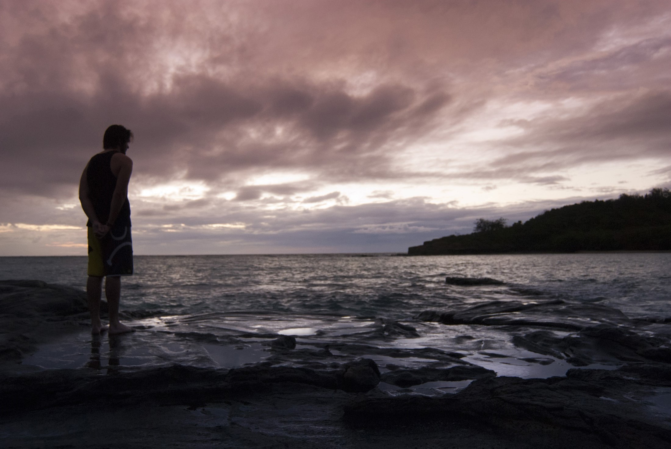 Man in silhouette standing on the seashore watching a marine sunset with clouds tinted a lilac purple