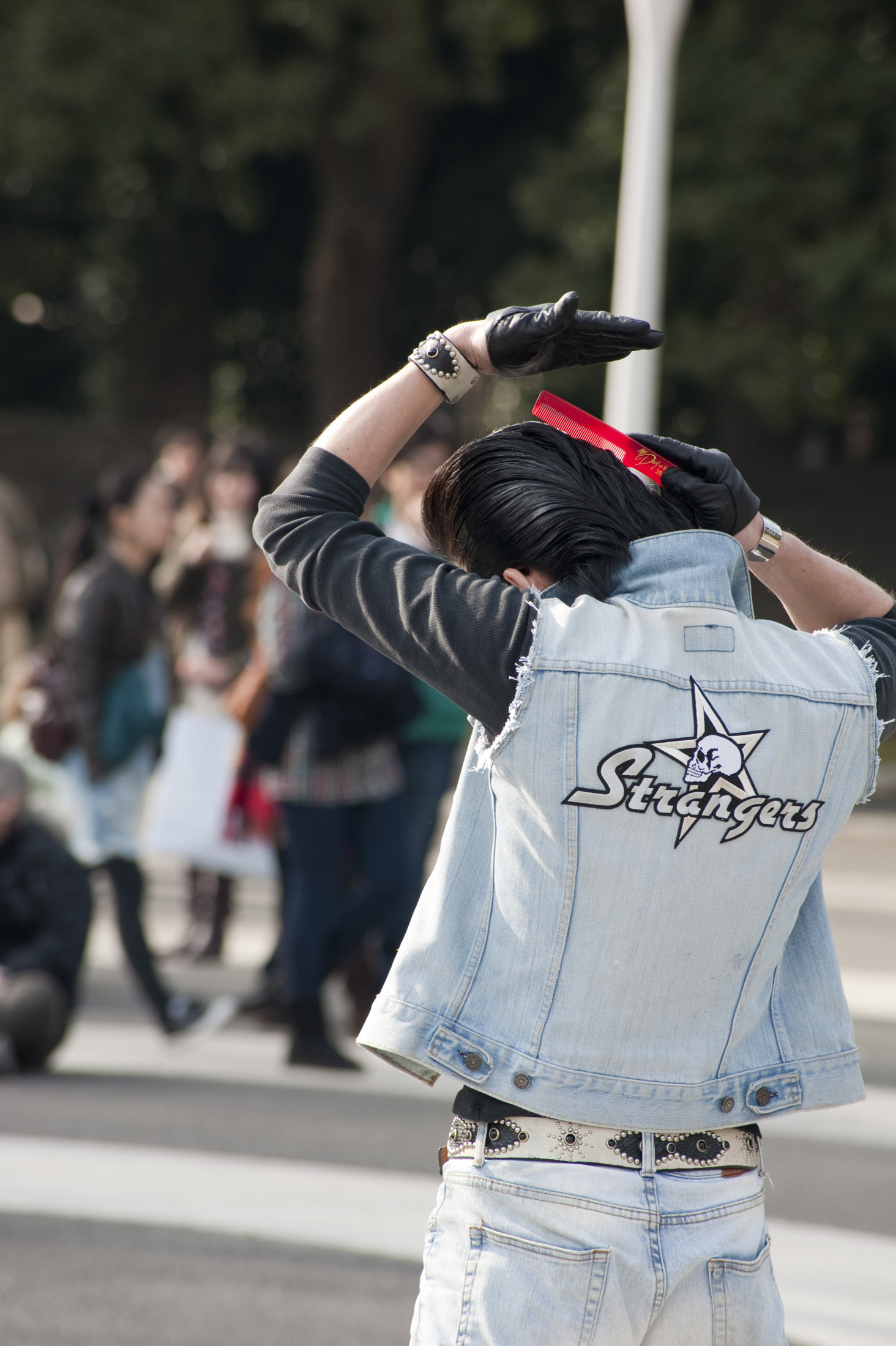 A rocker in Tokyos Yoyogi Park tends his hair - not model released