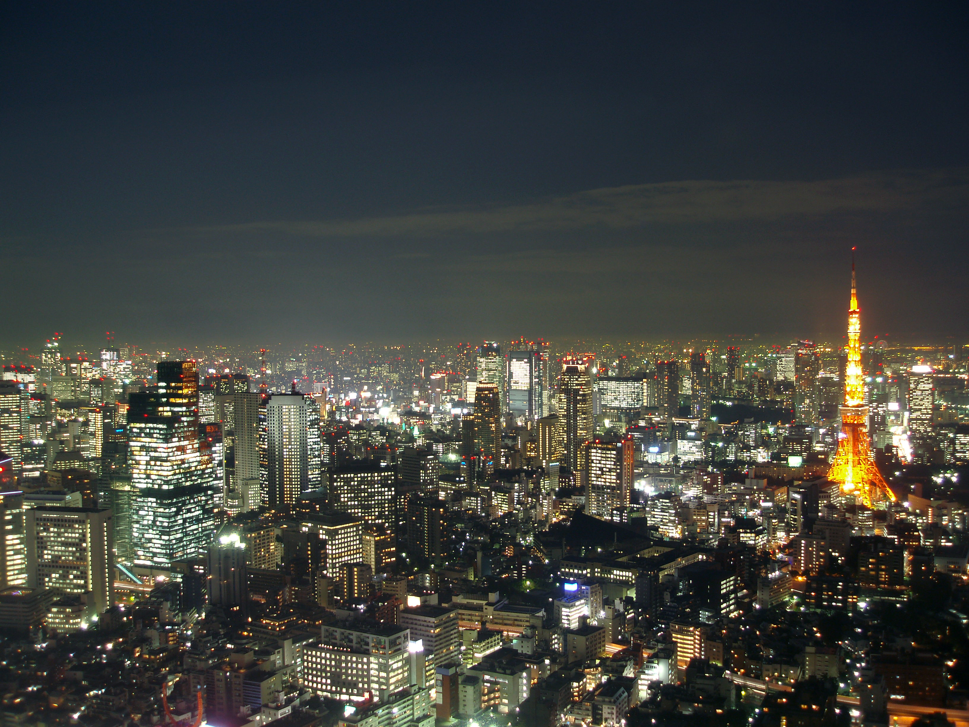view of tokyo tv tower and surrounding areas at night the the tower illuminated