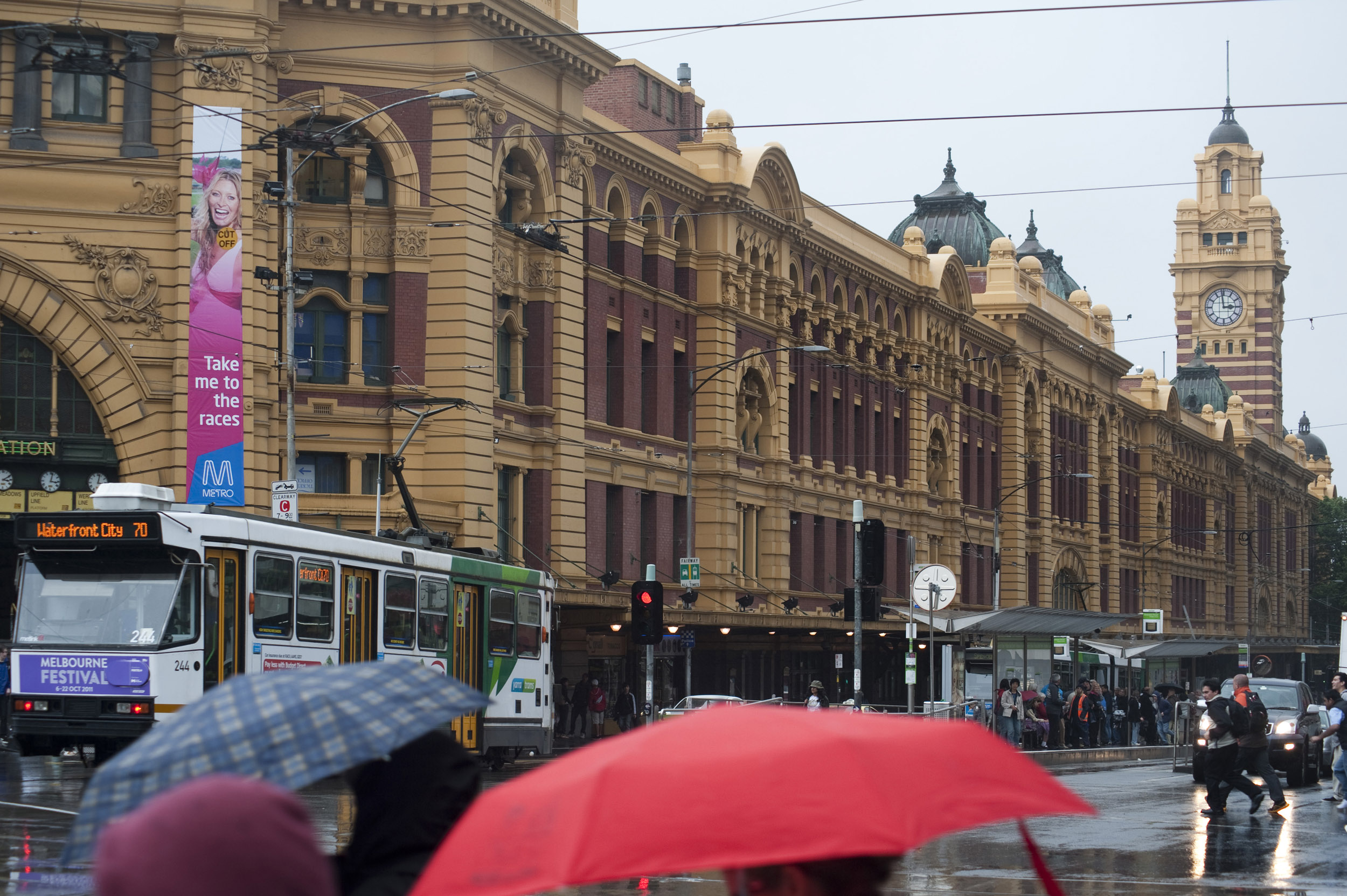 A busy winter scene and umbrellas on Flinders street in Melbourne city, Australia.
