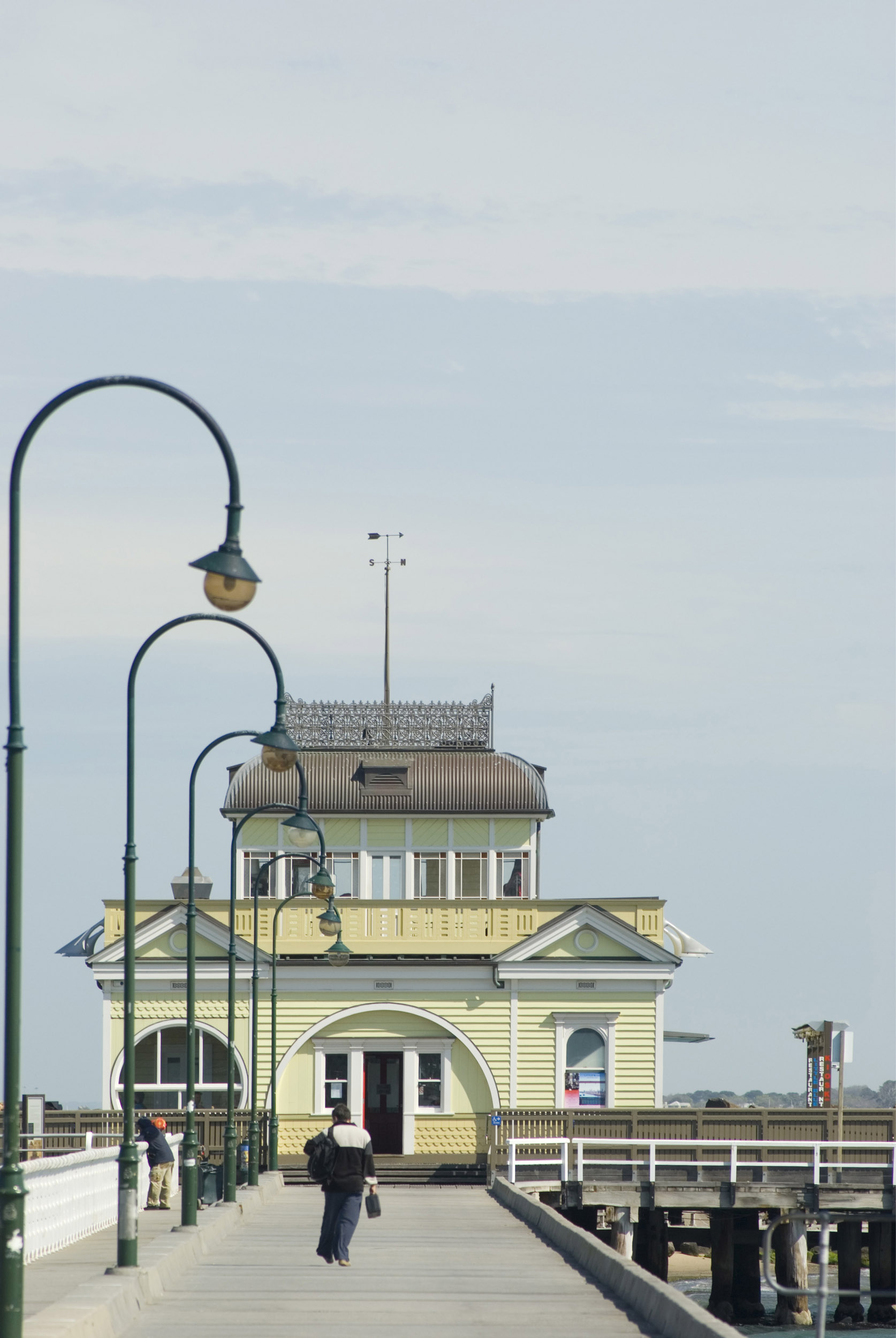 A historic, old fashioned building and hanging light poles at the Saint Kilda Pier in Victoria, Australia.