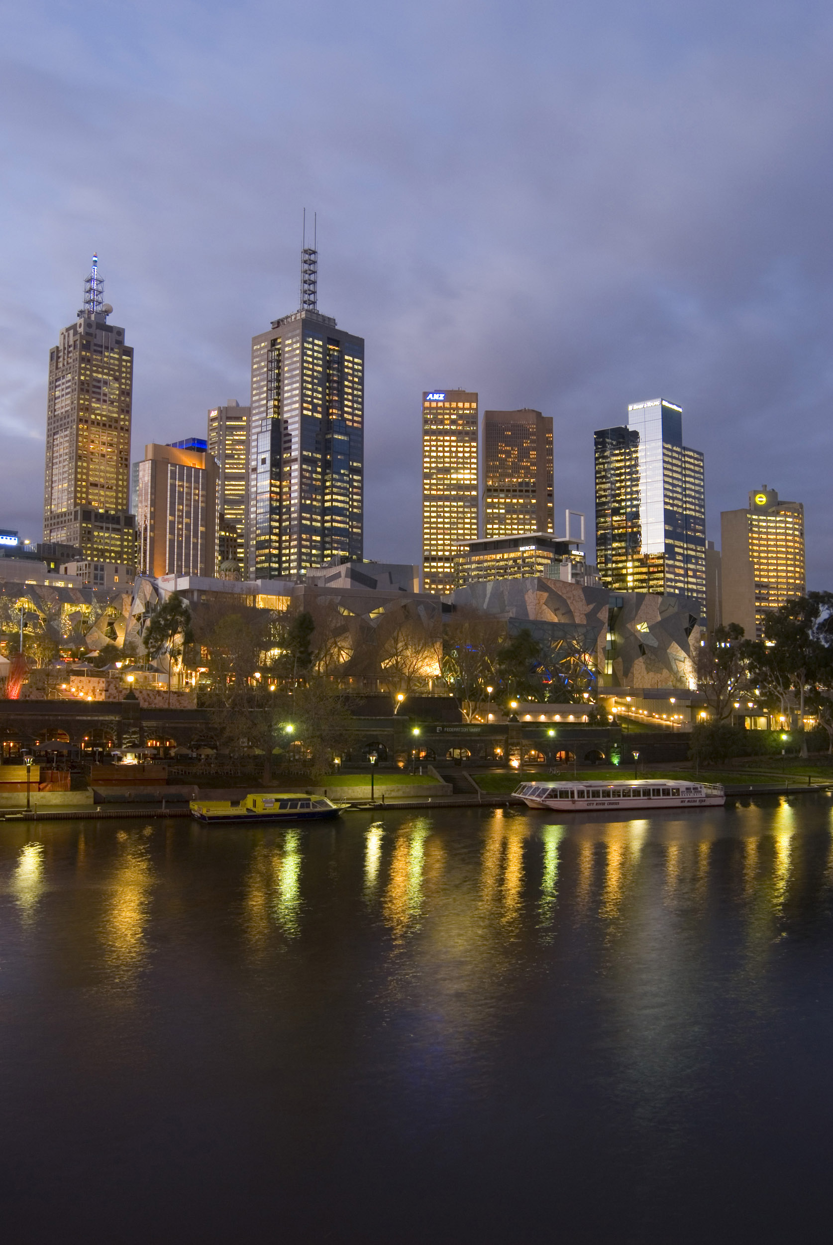 A portrait of the beautiful Yarra River and illuminated Melbourne city skyscrapers at night.