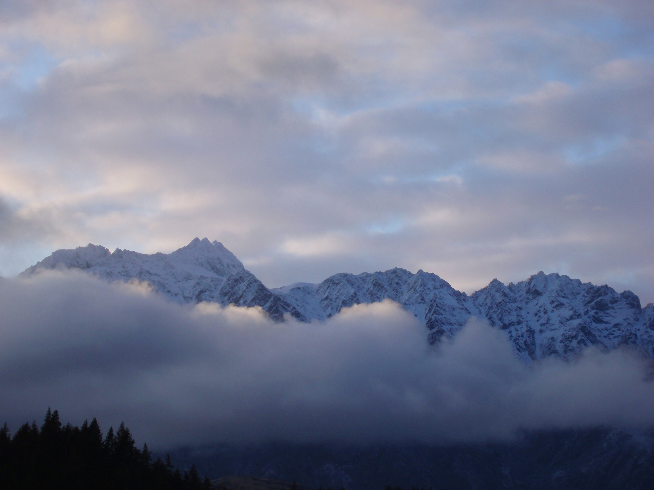 clouded montain range, the remarkables as seen from queenstown, newzealand in winter