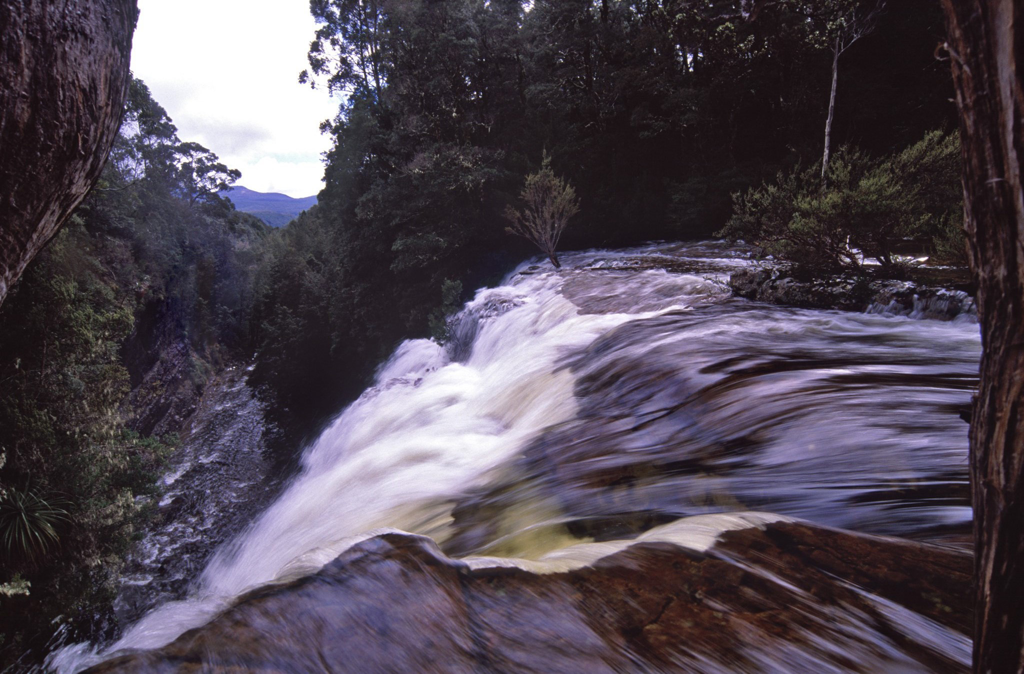 Fast flowing waterfall in Tasmania, Australia on the overland track with a close up view of the water cascading over a rock cliff to the river below