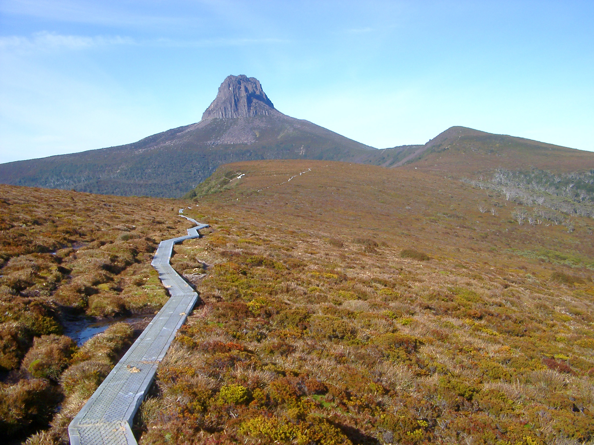 Wide Landscape and a Track to Famous Barn Bluff, A Mountain located in the Cradle Mountain-Lake St Clair National Park in the Central Highlands of Tasmania. Captured on Light Blue Sky Background.