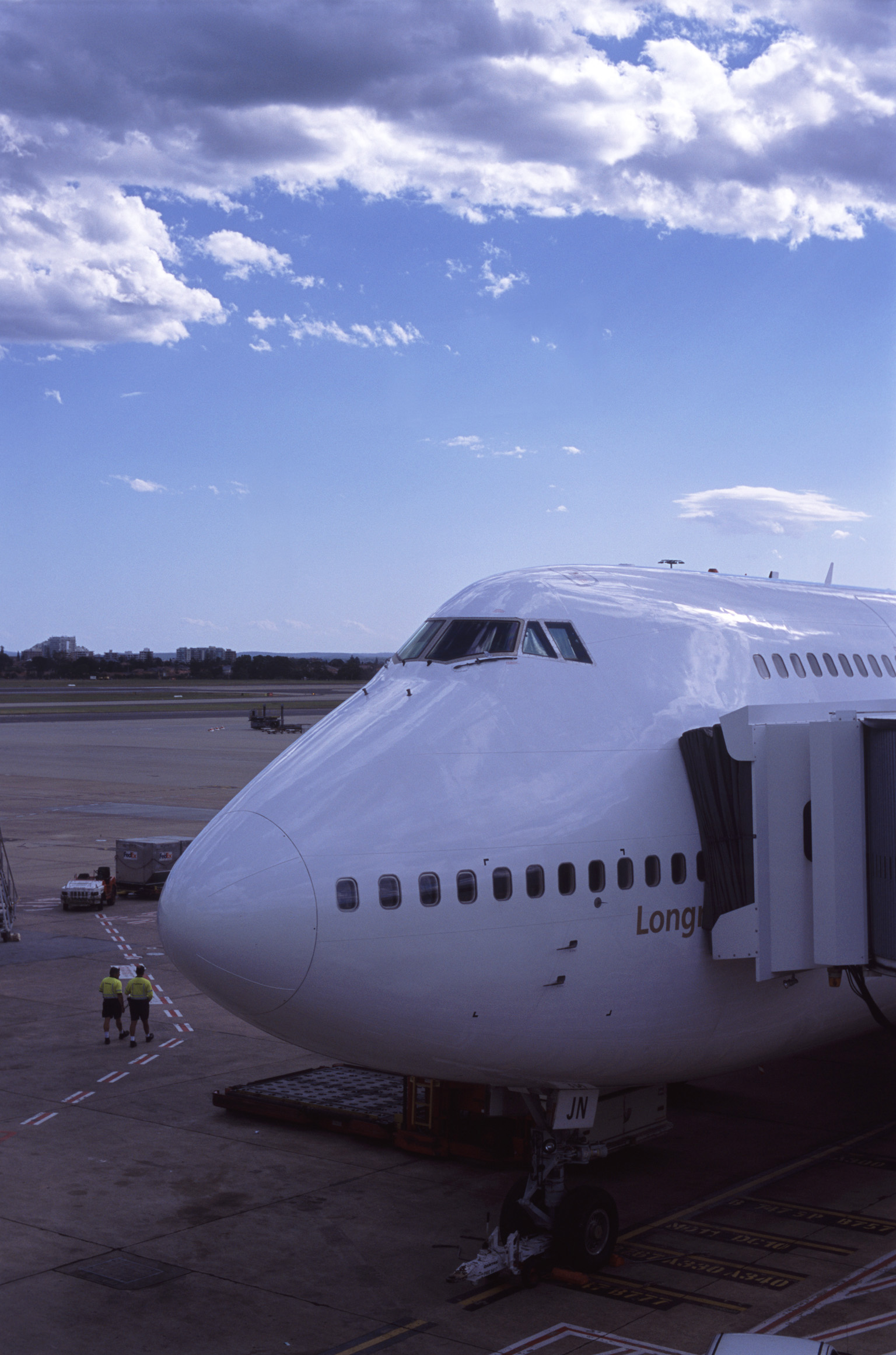 474 Jumbo aircraft loading for departure with a passenger skybridge attached to the side for embarkation as it stands on the apron at the airport
