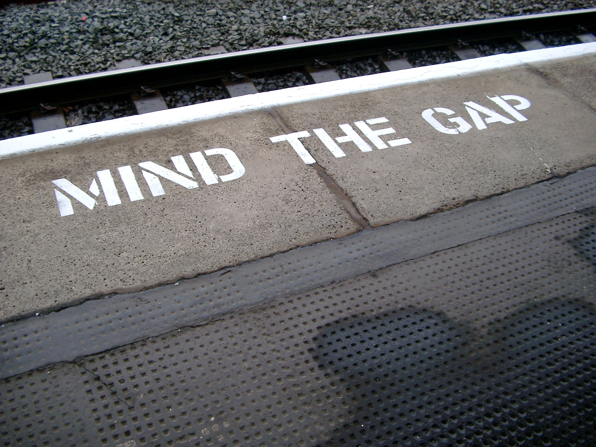 Platform edge at a train station with the warning - Mind The gap - painted in white on the edge of the tracks