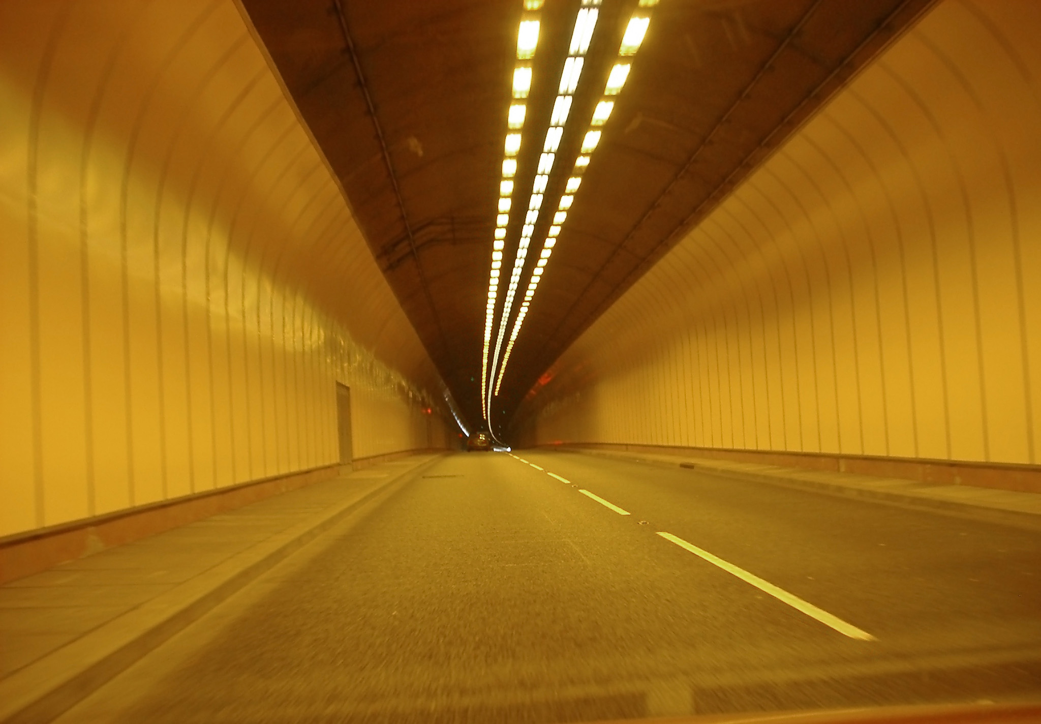 Road Level View of Road Tunnel with Yellow Lighting
