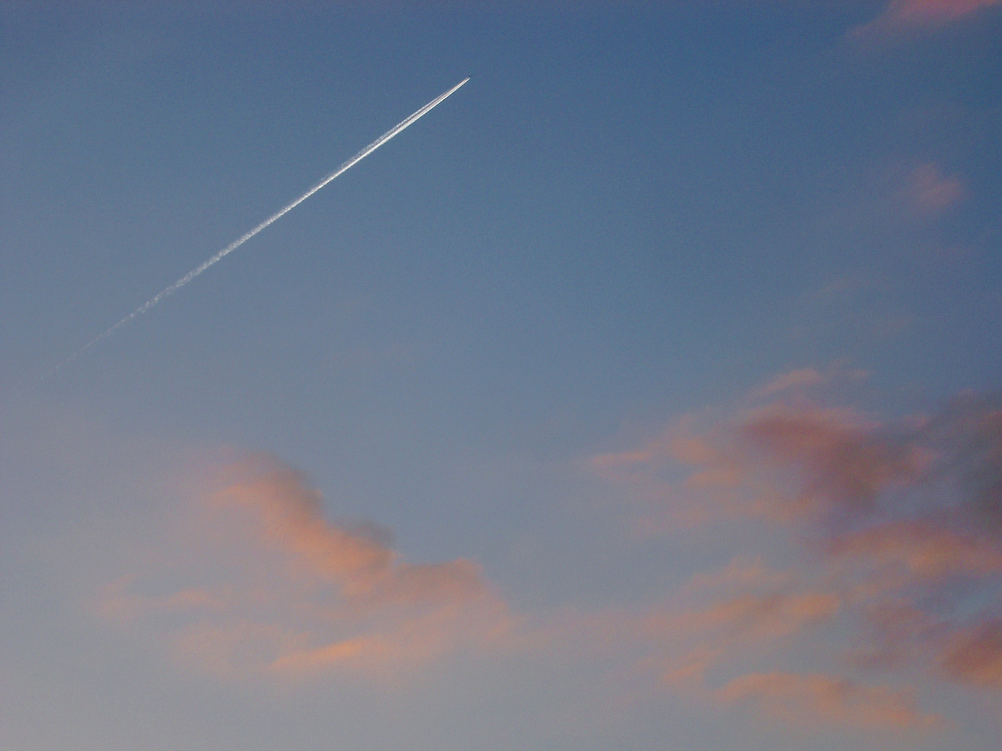 Jet trail or contrail formed by condensation of vapor and ice particles streaking through a blue sky at sunset with colorful pink clouds