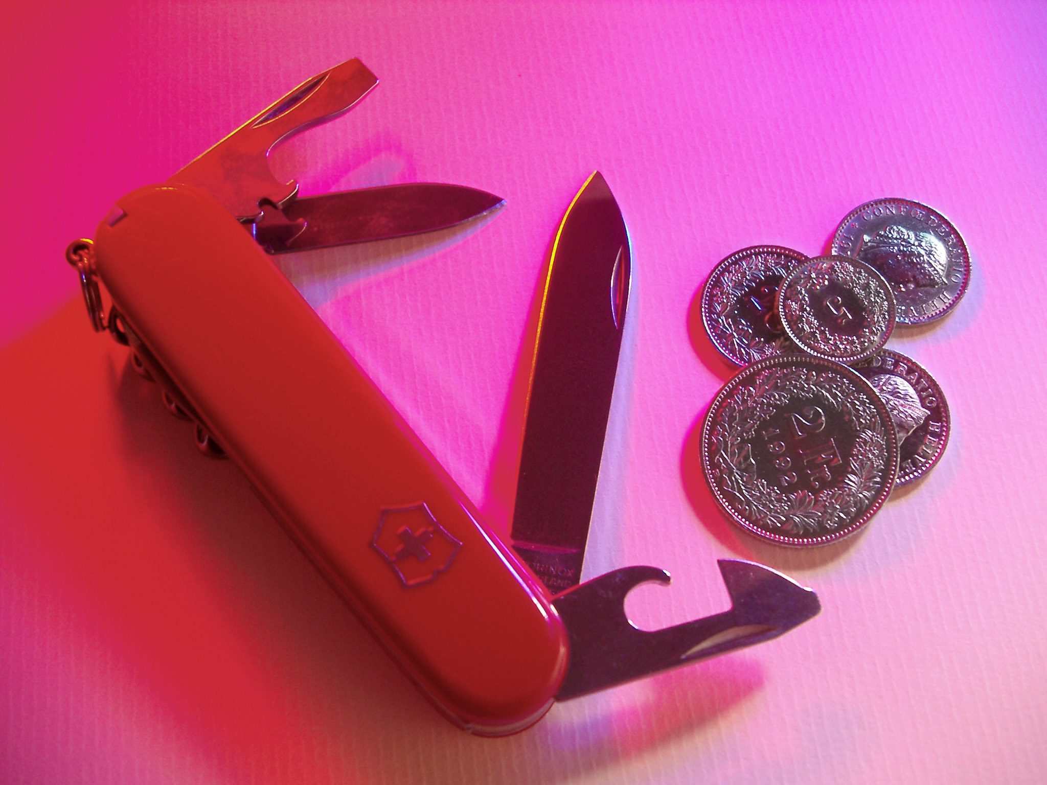 Swiss Army Knife with Swiss Francs on Pink Background Shot from Above