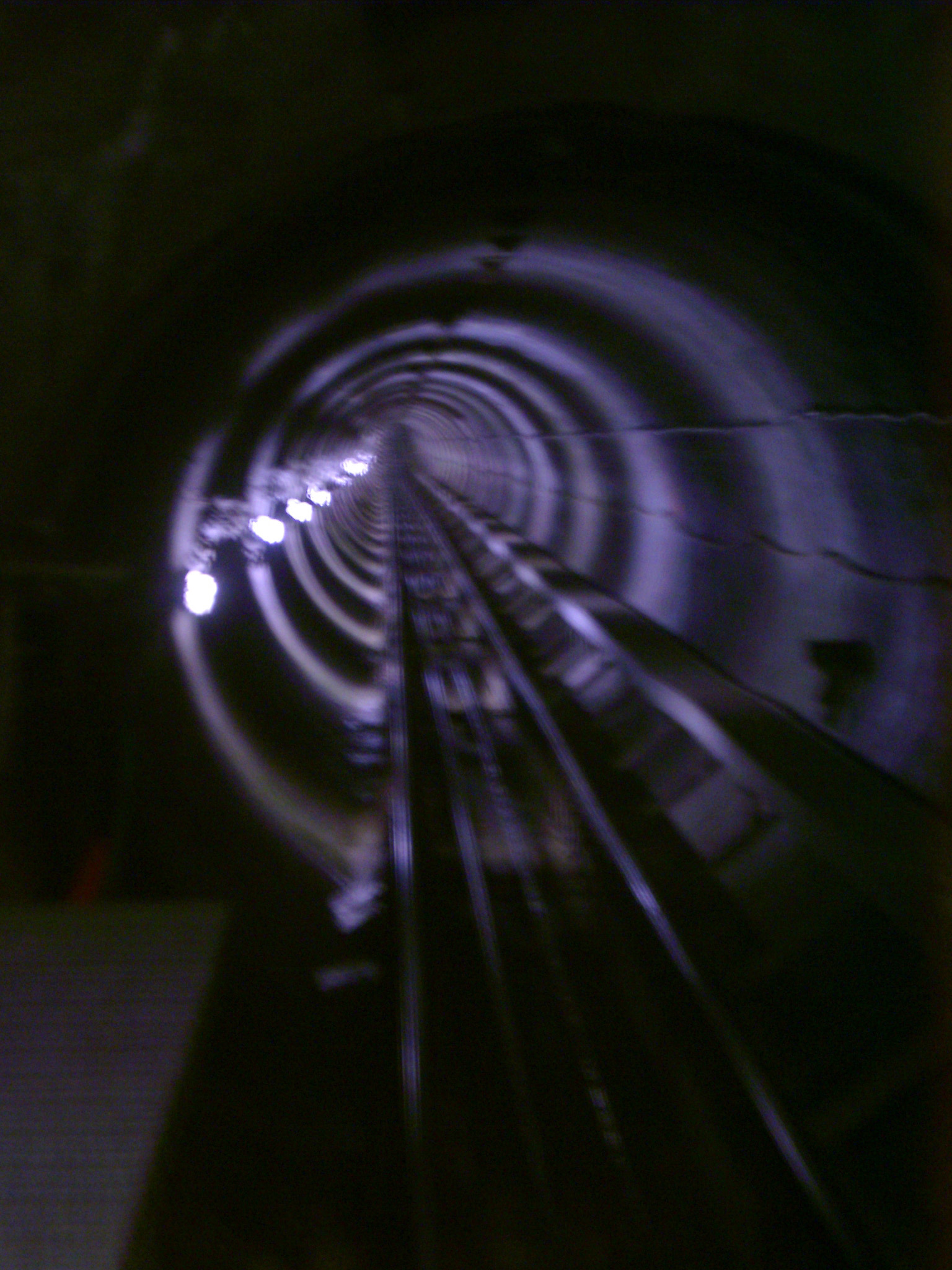 Blurred receding view of a rail tunnel taken from a moving train disappearing in to the darkness in a rail travel, commuting, and vacation concept