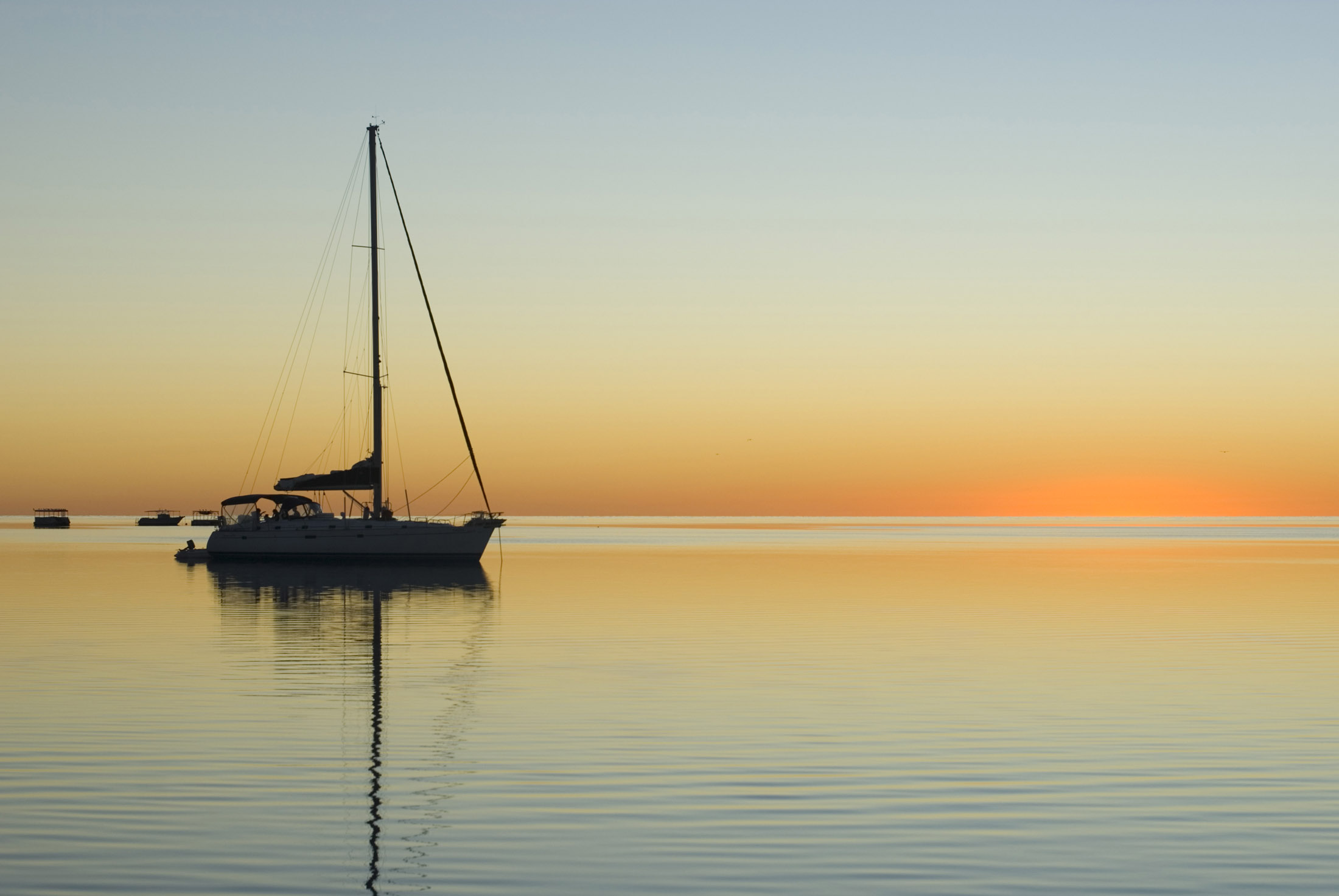 sunset over calm tropical waters with the silhouette of a sailing yacht