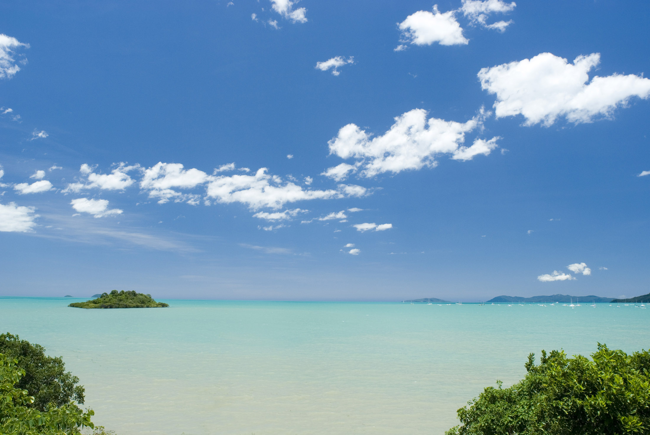 an oceanscape of crystal blue tropical waters with bluy sky and fliuffy clouds