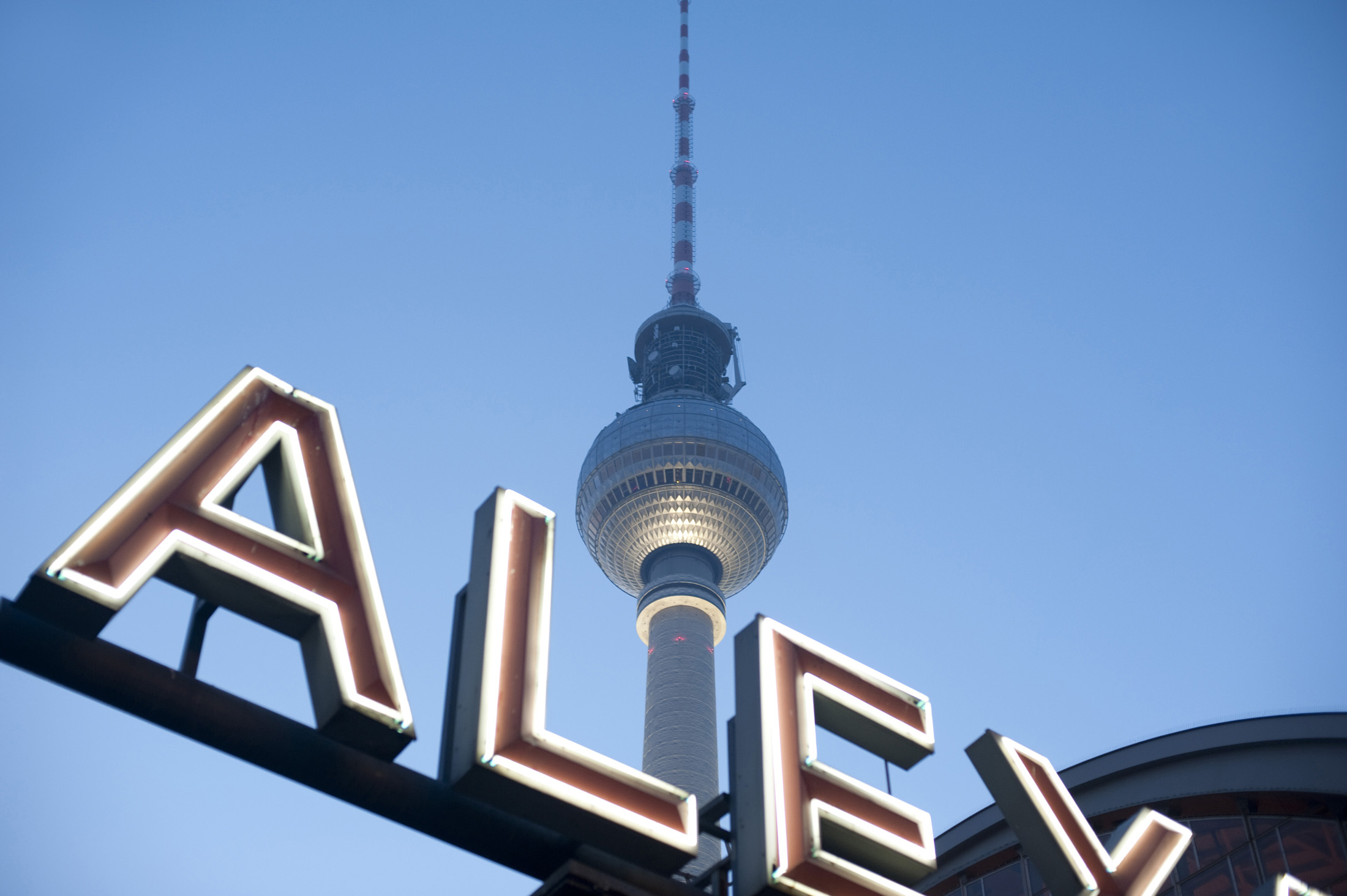 ther berlin fernsehturm tv tower and a neon sign at alexanderplatz