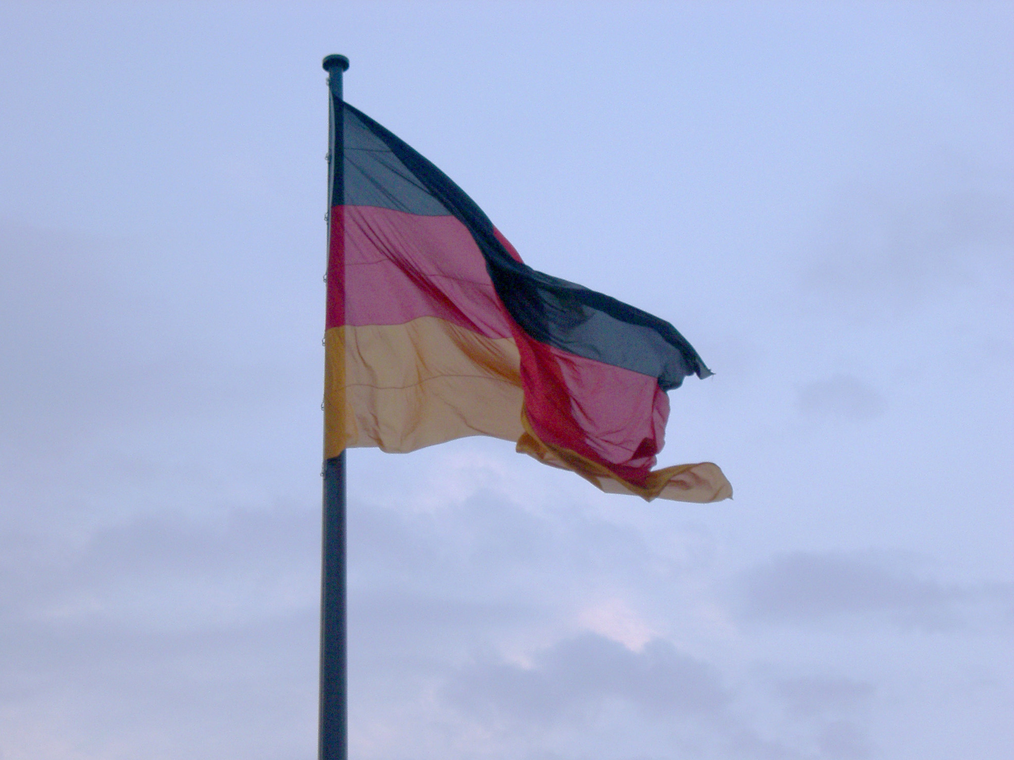 Flag of Germany fluttering in the wind against a cloudy sky, symbol of German national pride and identity