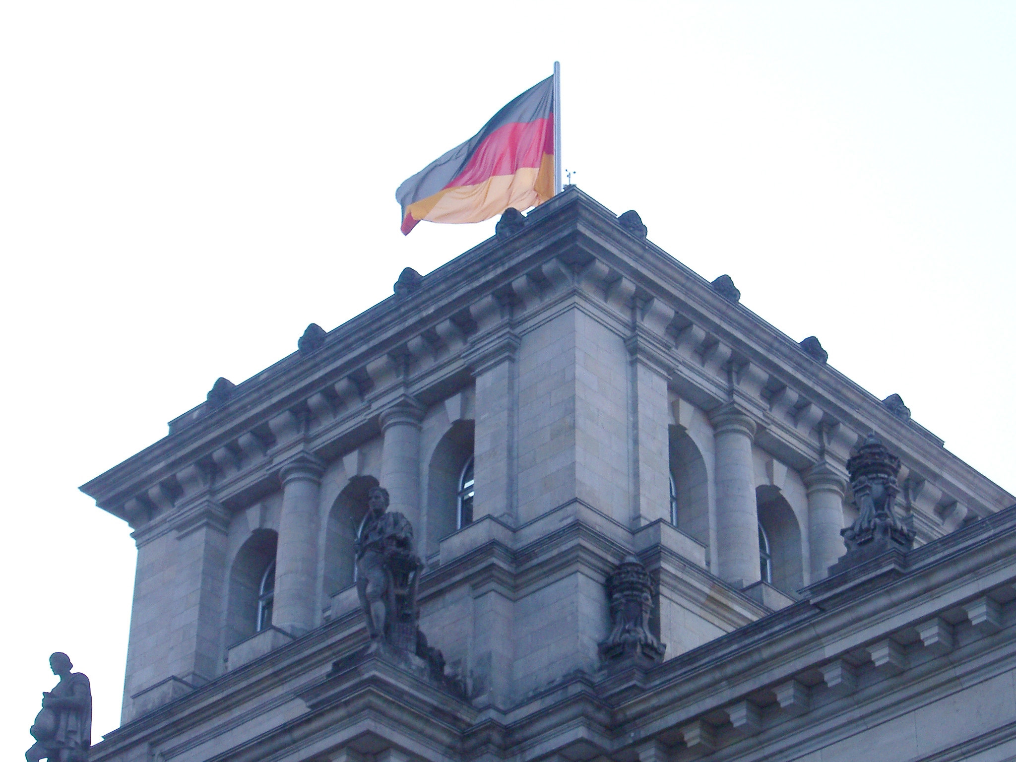 German flag flying at the Reichstag Building, the seat of the government in Berlin, against a bright sky