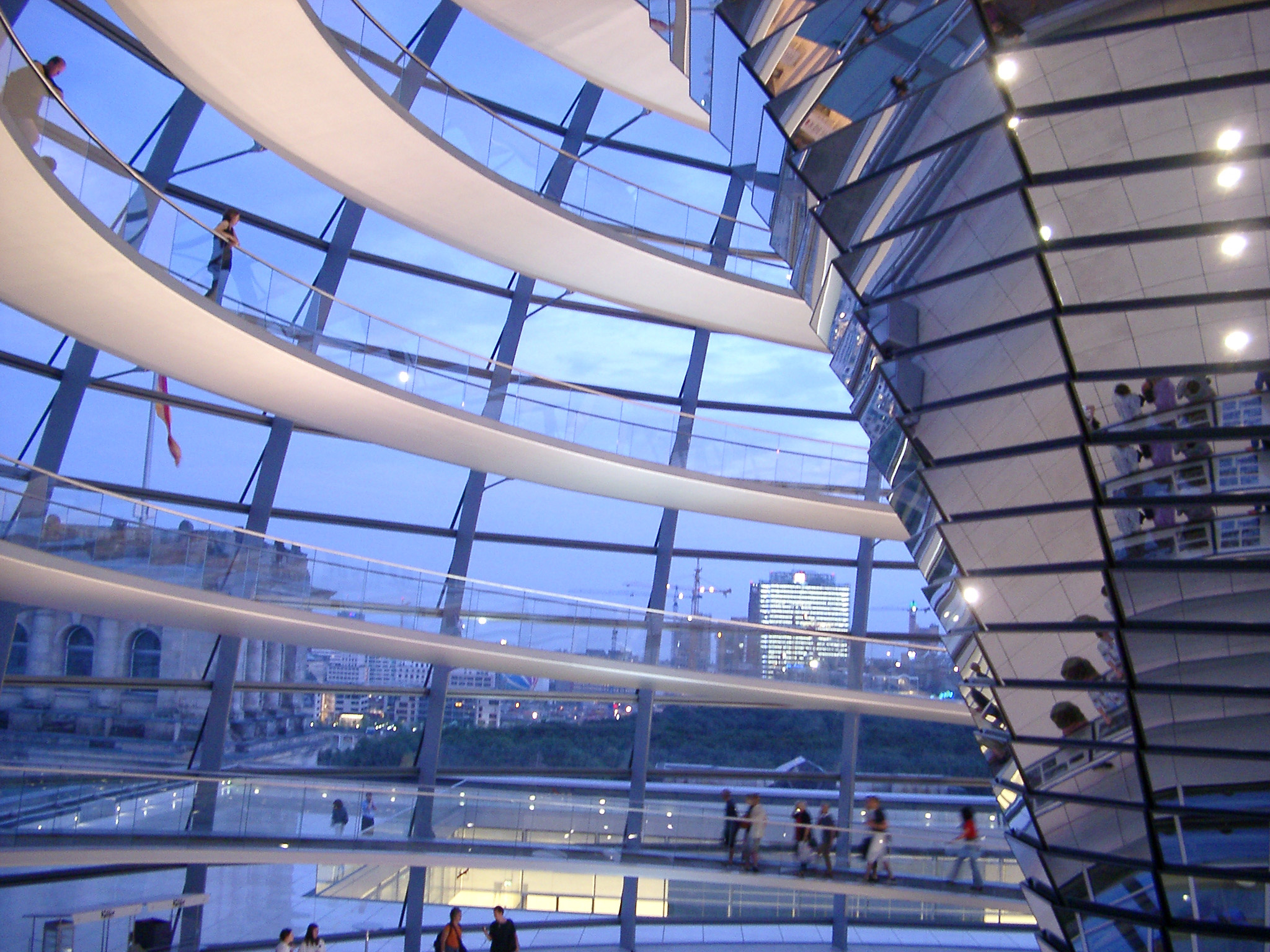 Inside the glass dome on the Reichstag building in Berlin offering a panoramic view of the city with tourists walking under the sunshades
