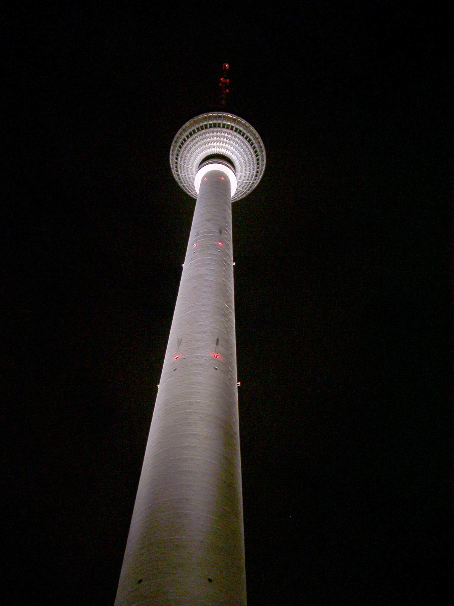 The Berliner Fernsehturm TV Tower at night viewed from the foot looking up to the sphere housing the restaurants and observation centre, illuminated against a dark night sky