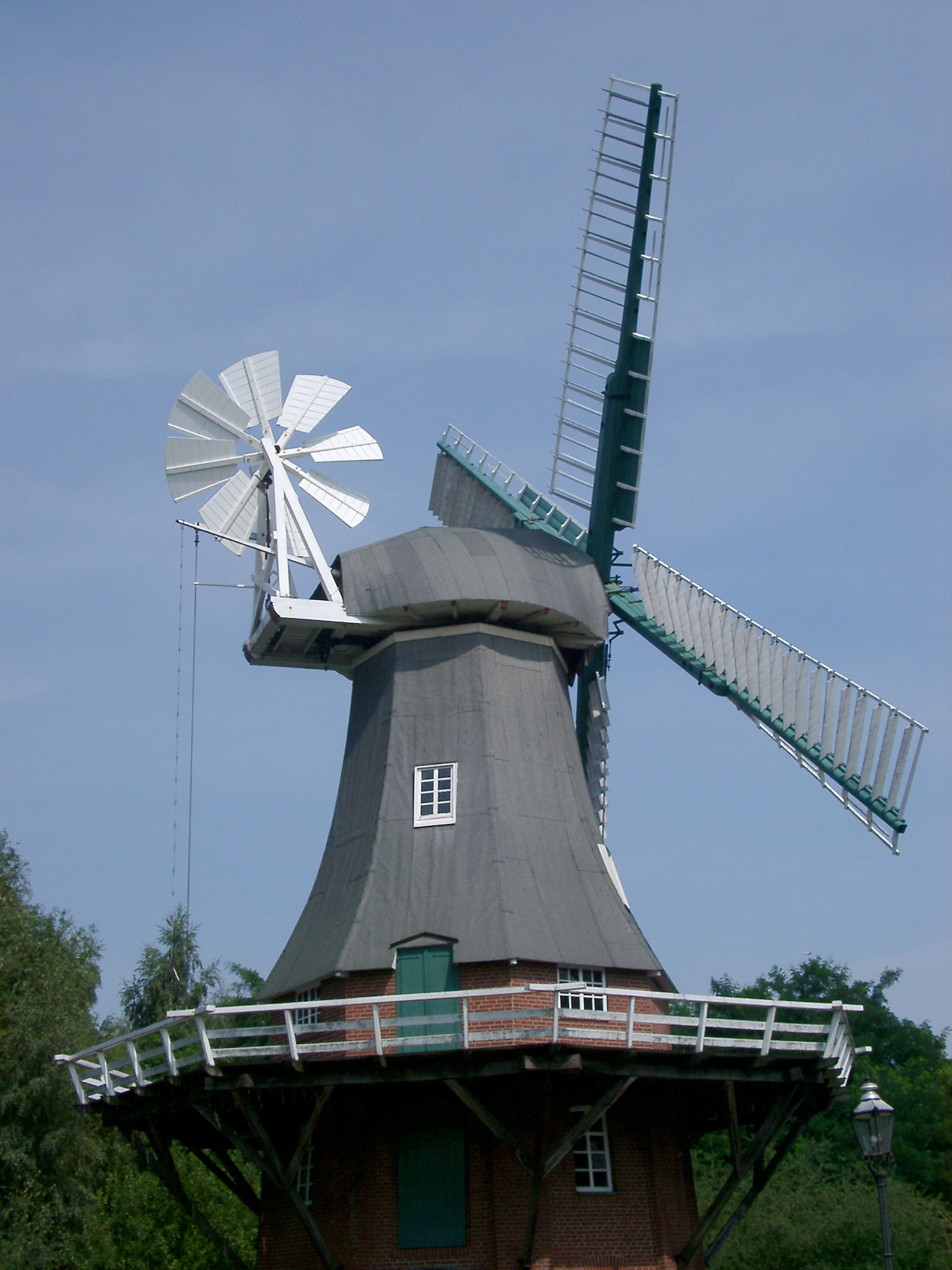 Historic windmill in Berlin with large wooden sails for converting kinetic energy from the wind and a secondary smaller windmill mounted on its side