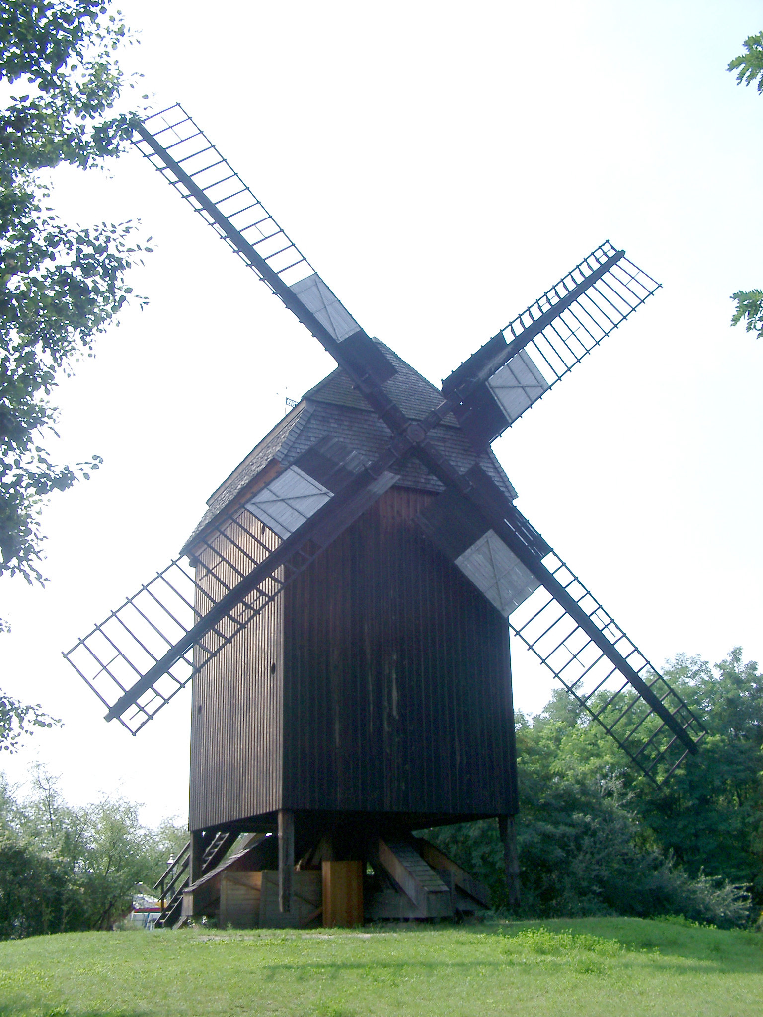 Historic square wooden windmill with large sails in Berlin, now a museum