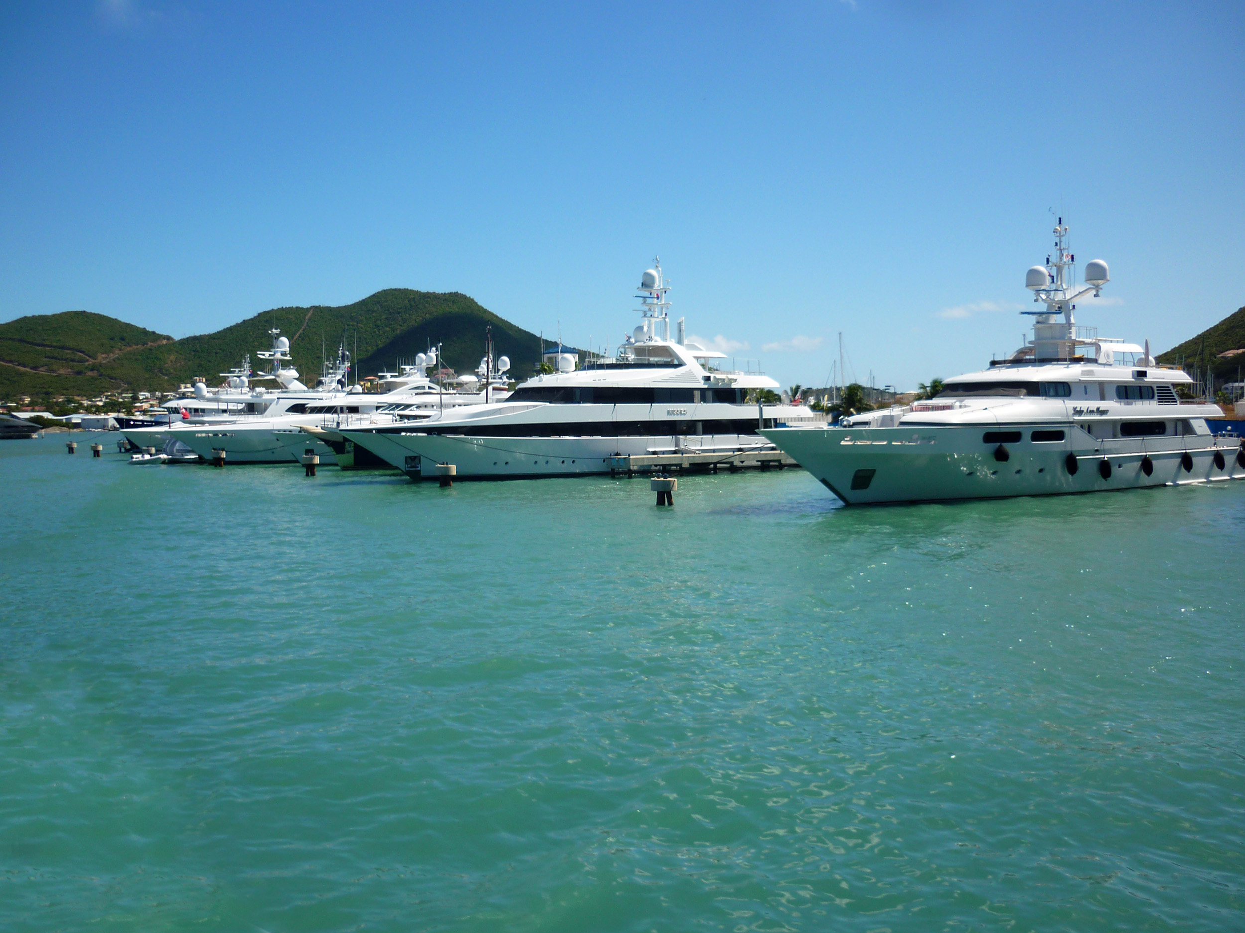 a line of super yachts docked on the caribbean island of st martin