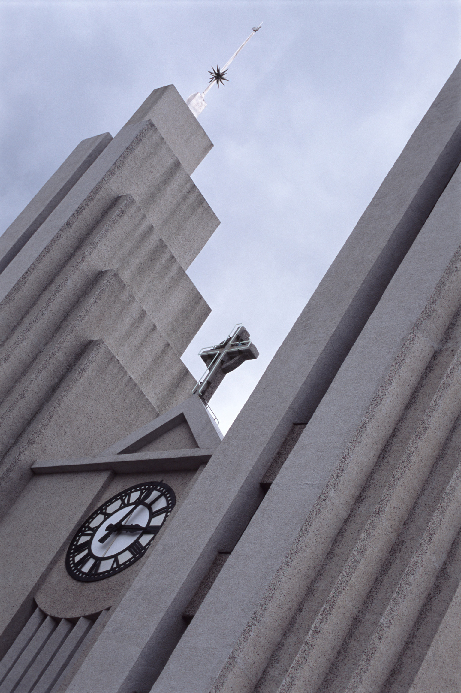 Close-up of the facade of the Lutheran Church of Akureyri, from Iceland, with a Christian cross mounted above the clock, concept of faith and time