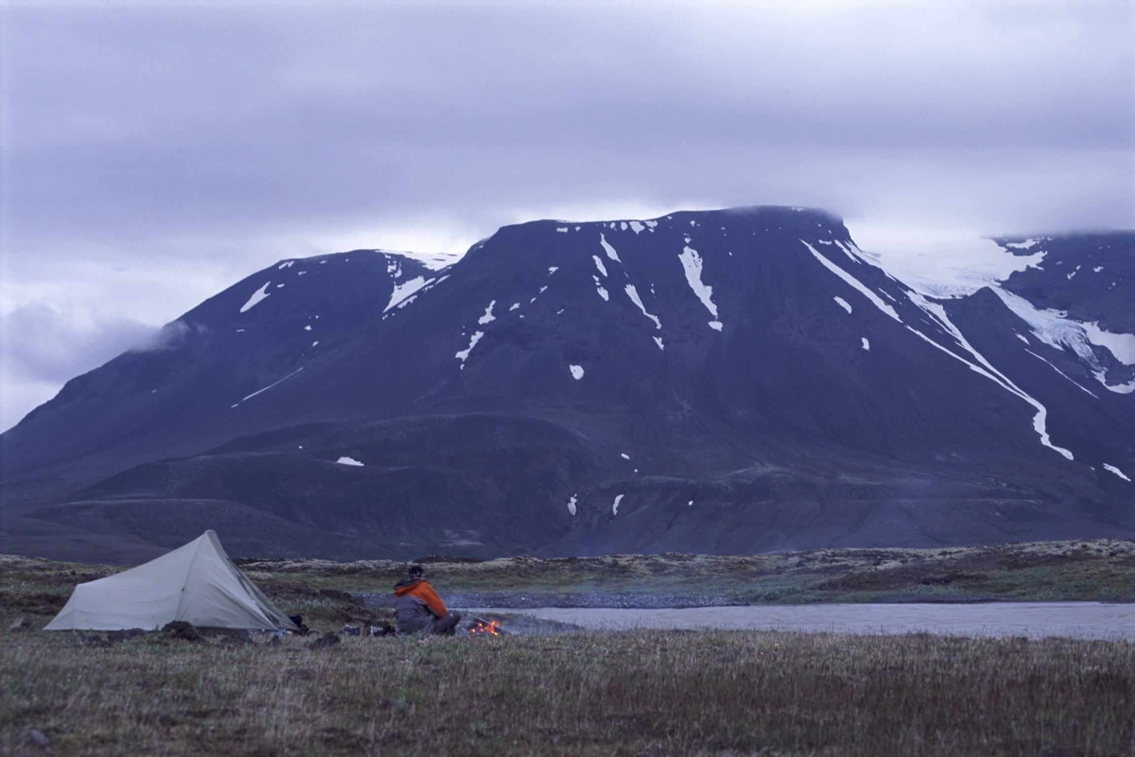 Camping in Iceland on the lowland plains below a snowy volcanic mountain range alongside a meltwater lake with a tent and person at a campfire