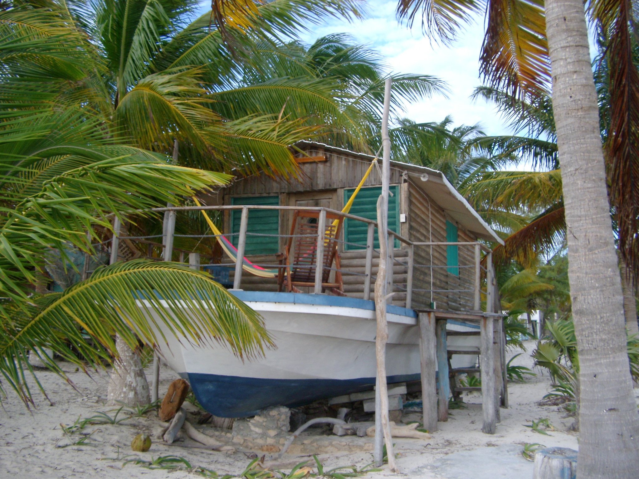 Wooden log cabin houseboat in Mexico sited on the golden sand of a tropical beach amidst palm trees