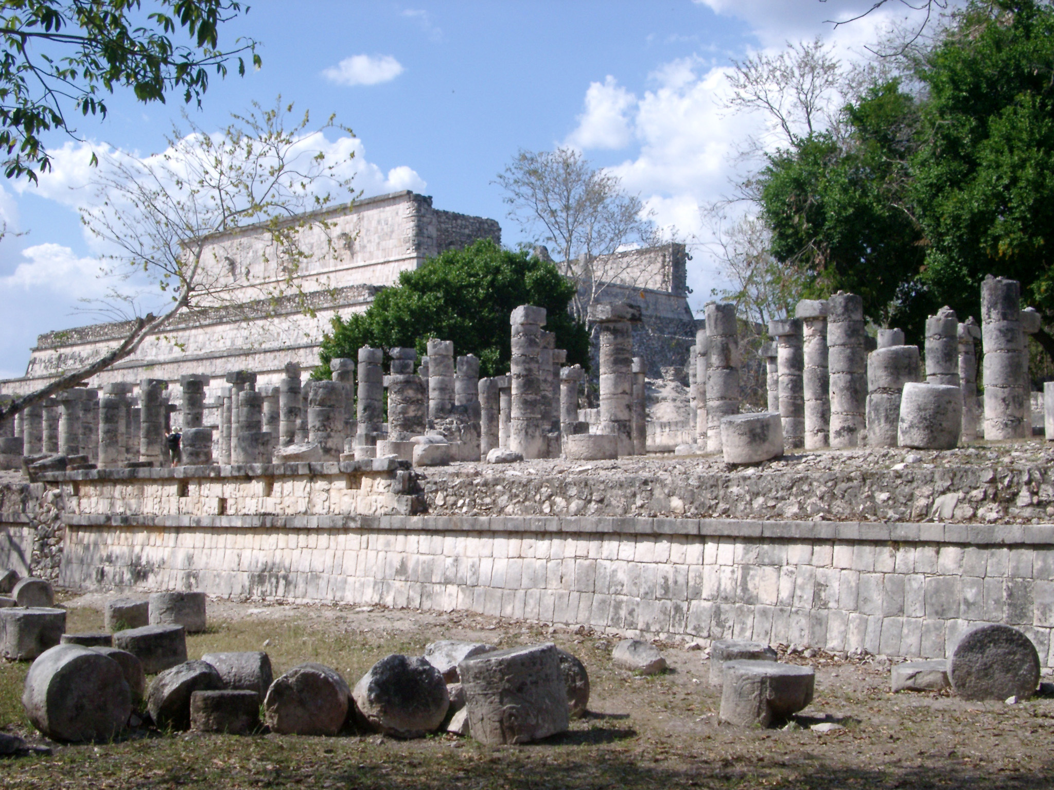 View of the stonework at the Chitzen Itza Mayan ruins with fallen stone, rows of columns and the Temple of the Warriors in the background, Yucatan Peninsula, Mexico