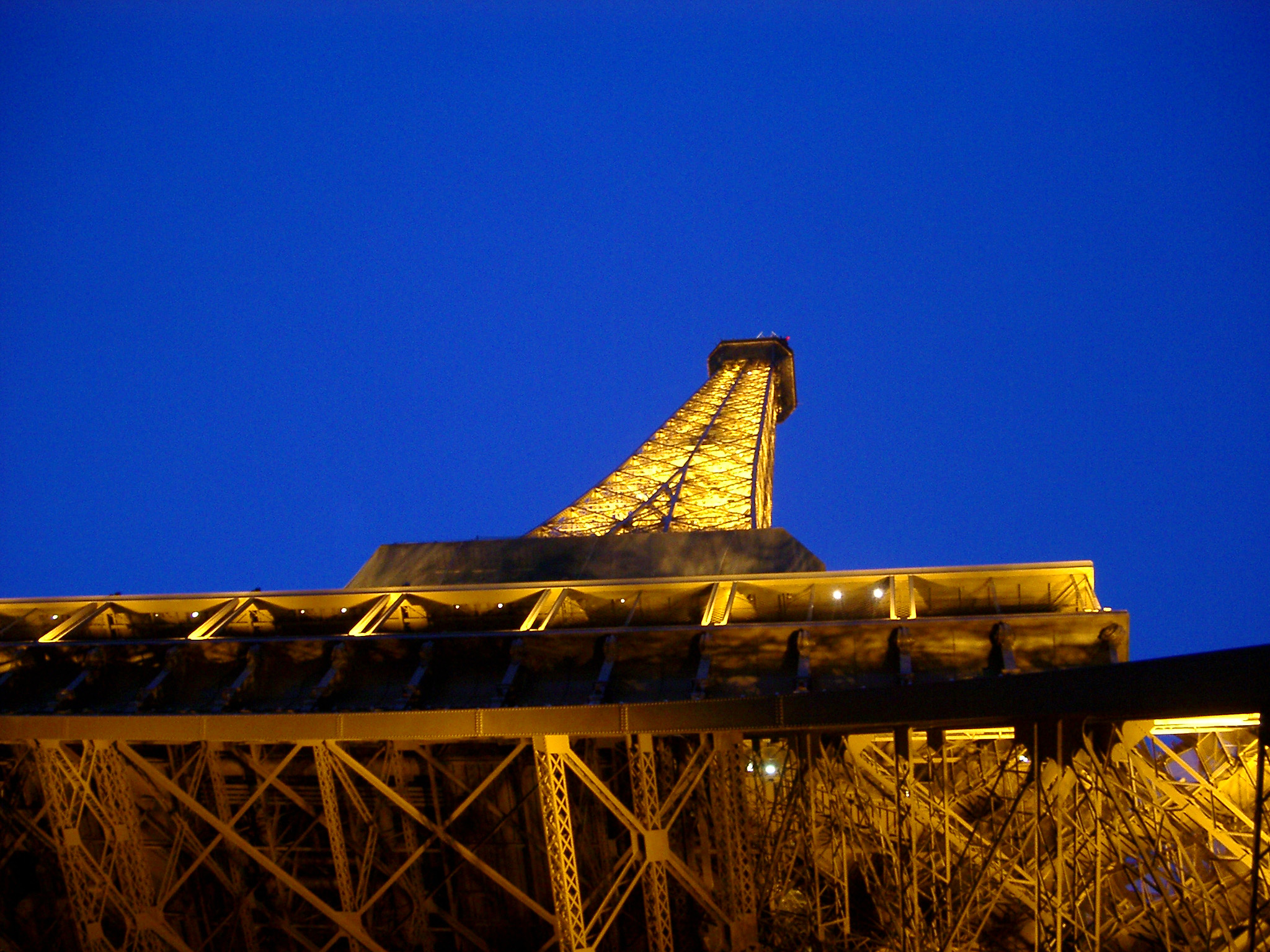 Looking Up at Eiffel Tower with Lights On Against Blue Night Sky, Paris, France