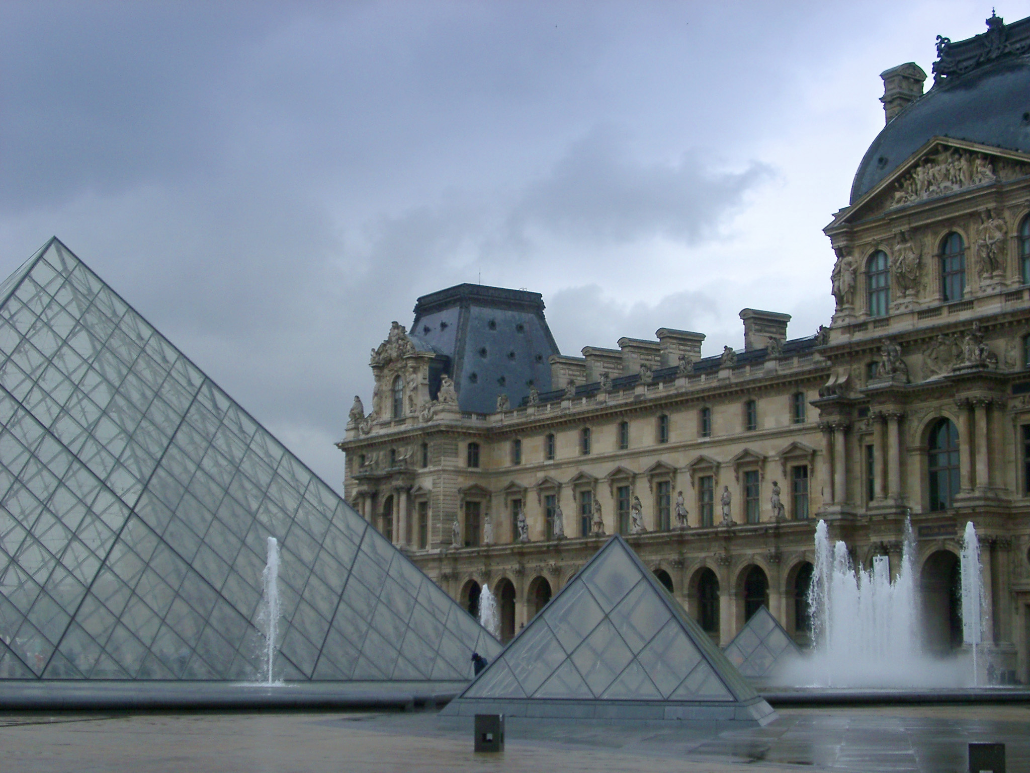 Courtyard of the Louvre in Paris showing the ornamental fountains and glass modern pyramids backed by the stone facade of the museum