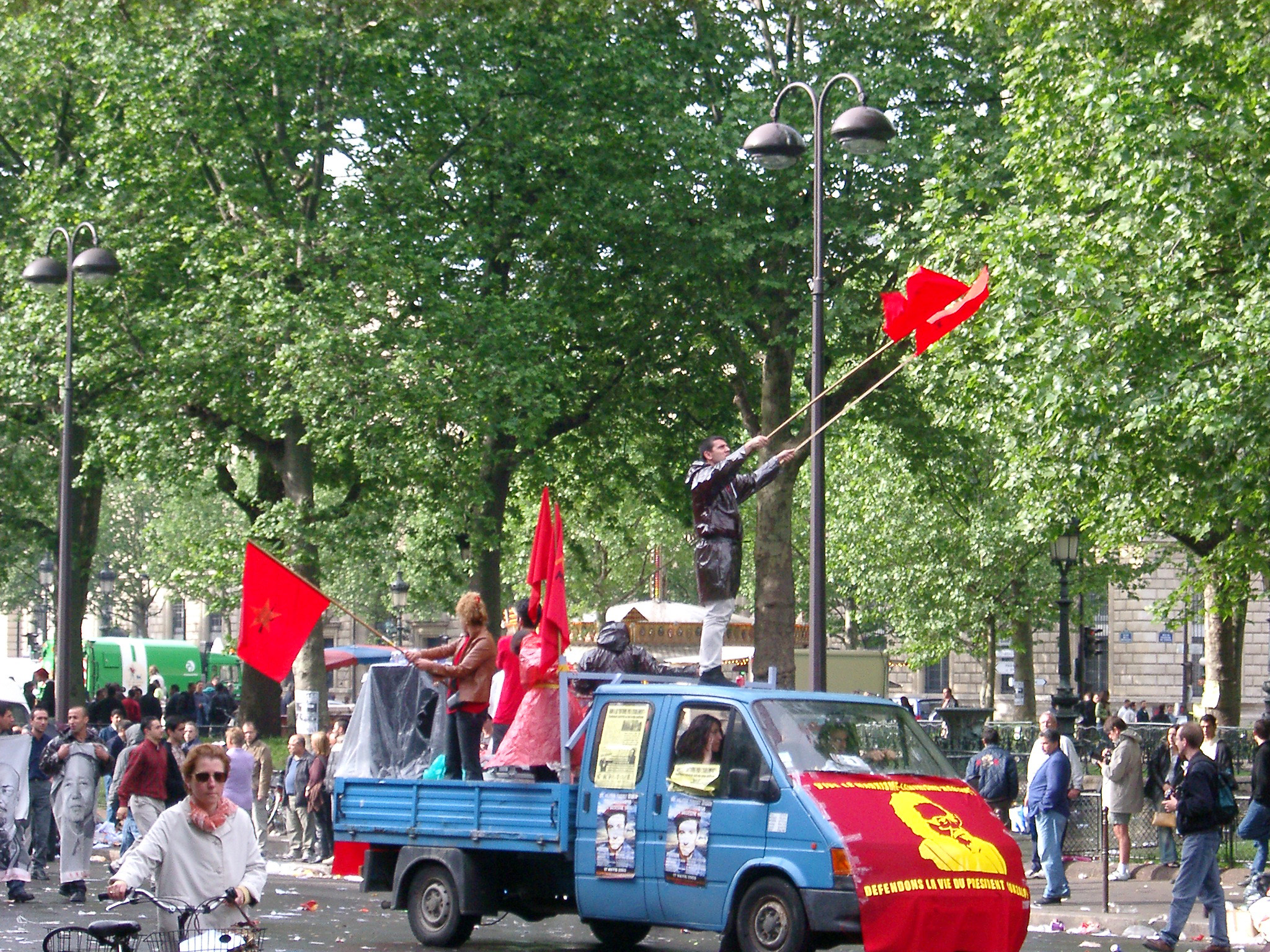 Men with Flags on Vehicle with Random People on Ground During May Day Parade. Isolated on Tall Green Trees.