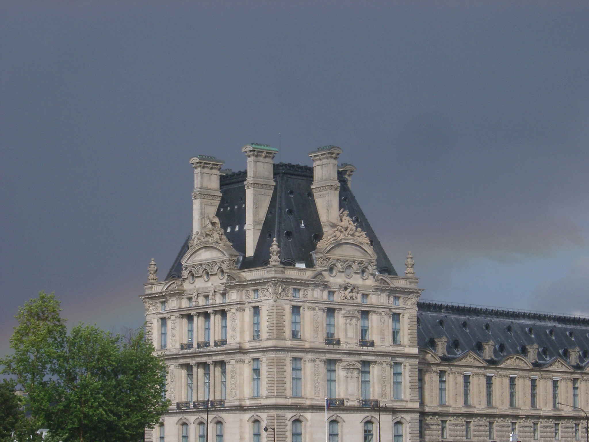 Paris rainbow in a rainy stormy grey sky behind an imposing historical urban stone building