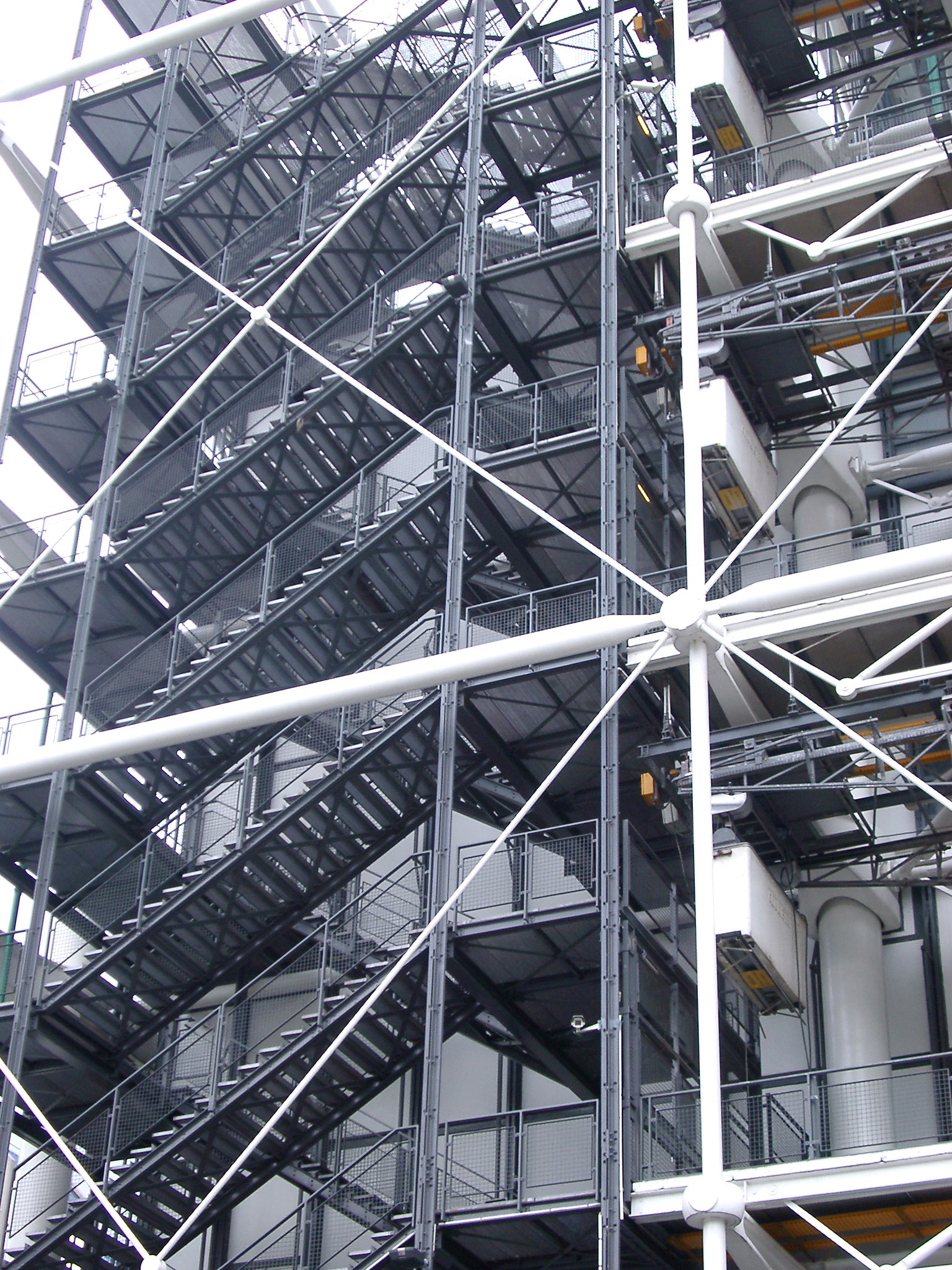 Exterior of the Georges Pompidou building showing a series of metal staircases or fire escapes on the modern glass facade