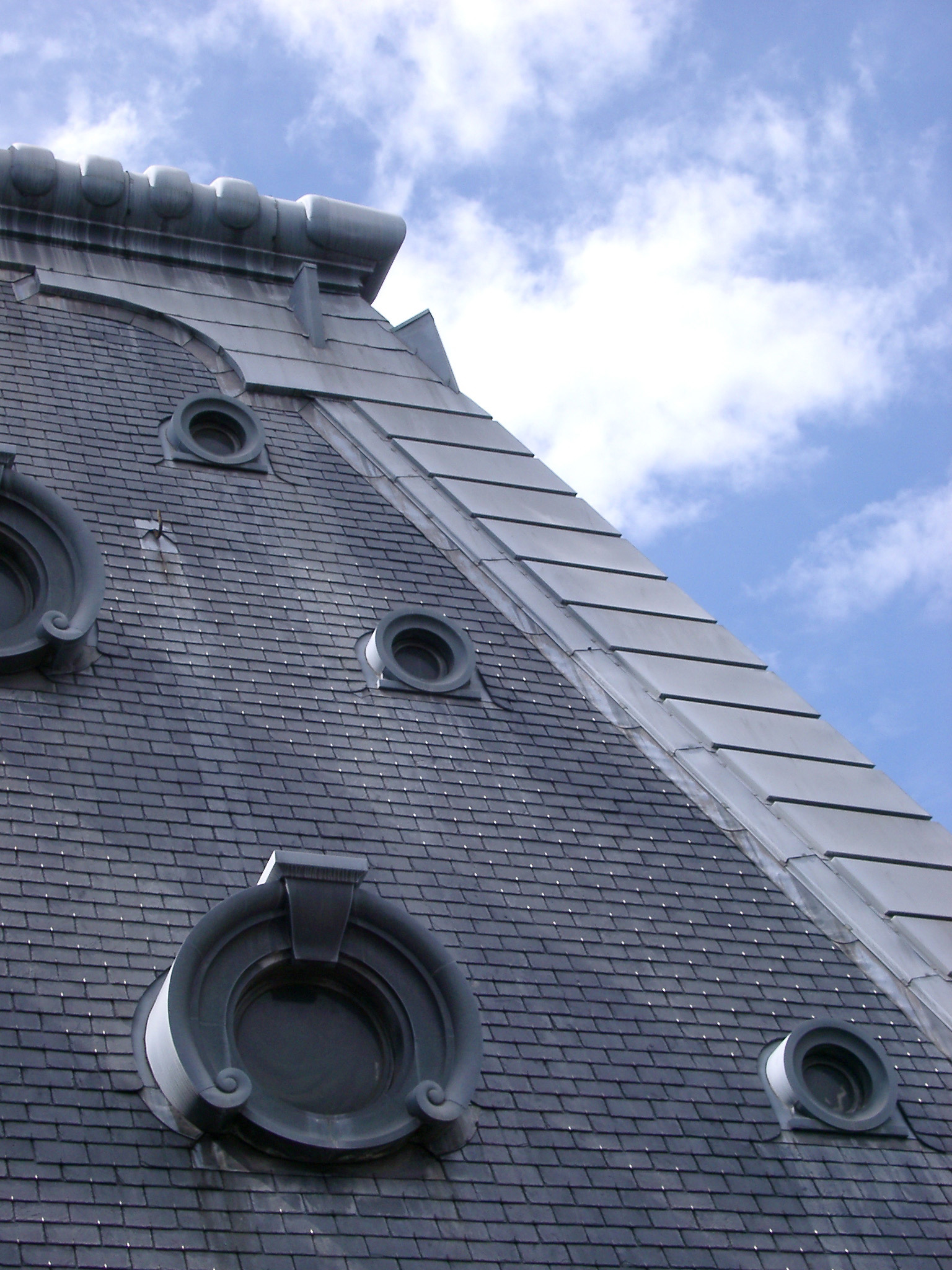 Close up of French Roof Details aginst Light Blue and White Sky Background