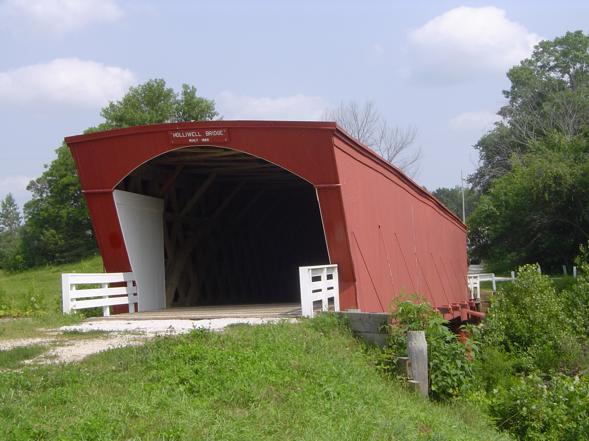 Close up Covered Bridge Surrounded by Green Grasses and Tall Trees on Lighter Blue Sky Background.