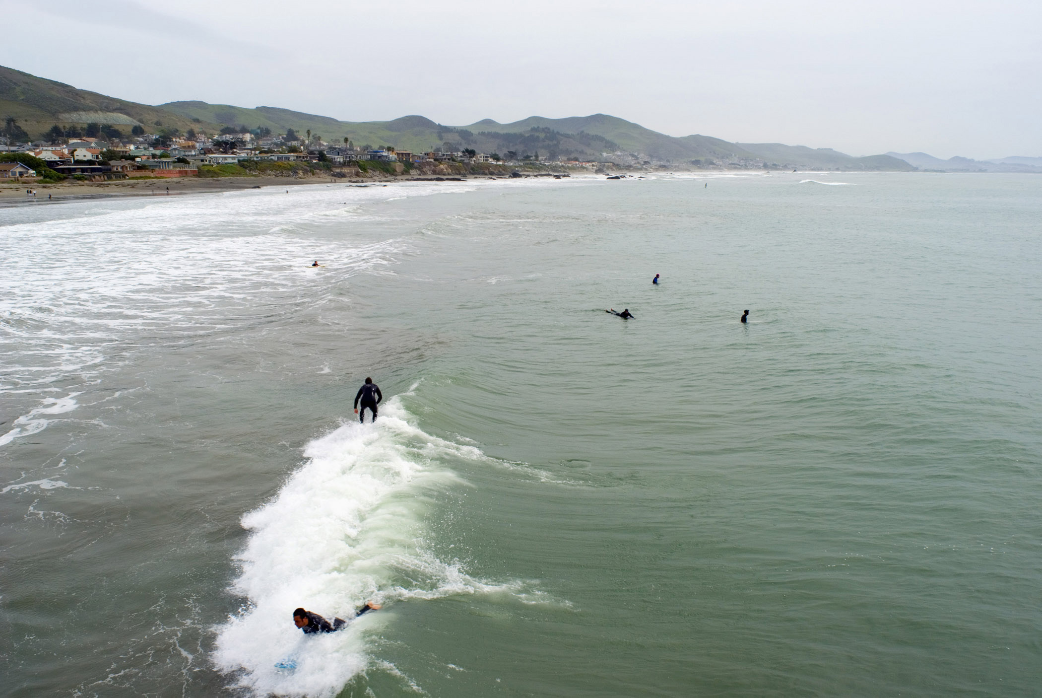 Overview of Surfers catcing the waves at Cayucos State Beach, California, USA