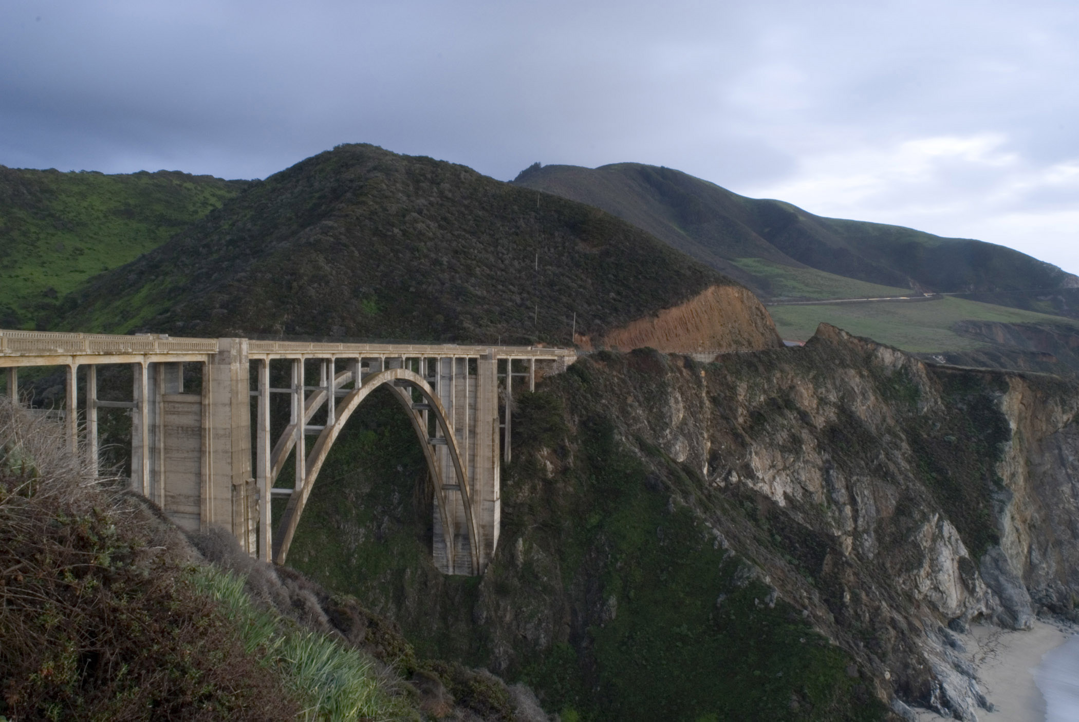 Scenic view of the steep rocky cliffs on the Big Sur coastline in Californa with the concrete arch of the Bixby Creek road bridge