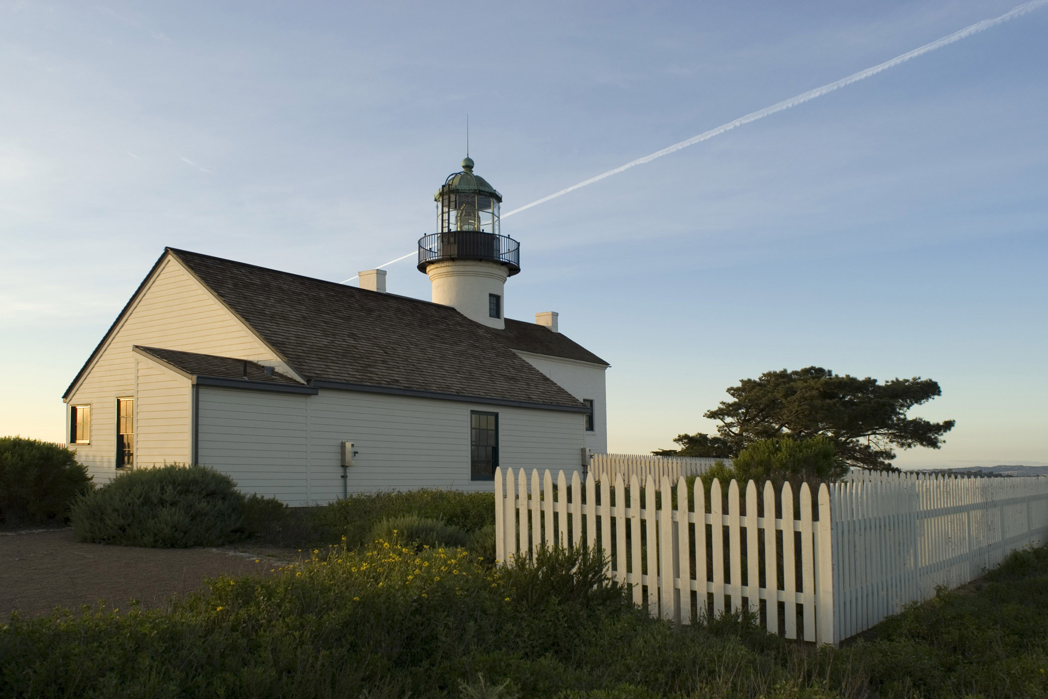 Old Point Loma Lighthouse Surrounded by Green Plants. Isolated on Light Blue Sky Background.