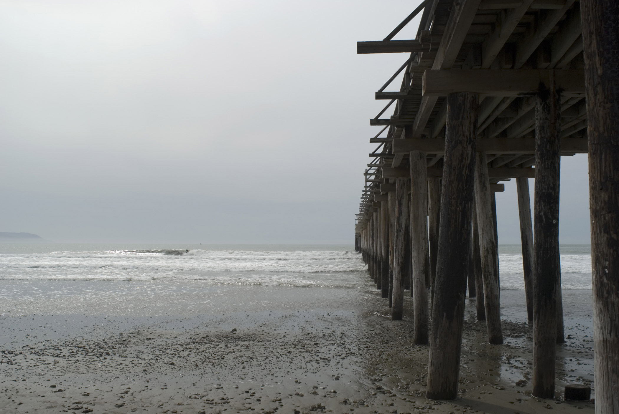 View Underneath the Wooden Columns at Cayucos Pier. Isolated on Light Gray Sky Background.